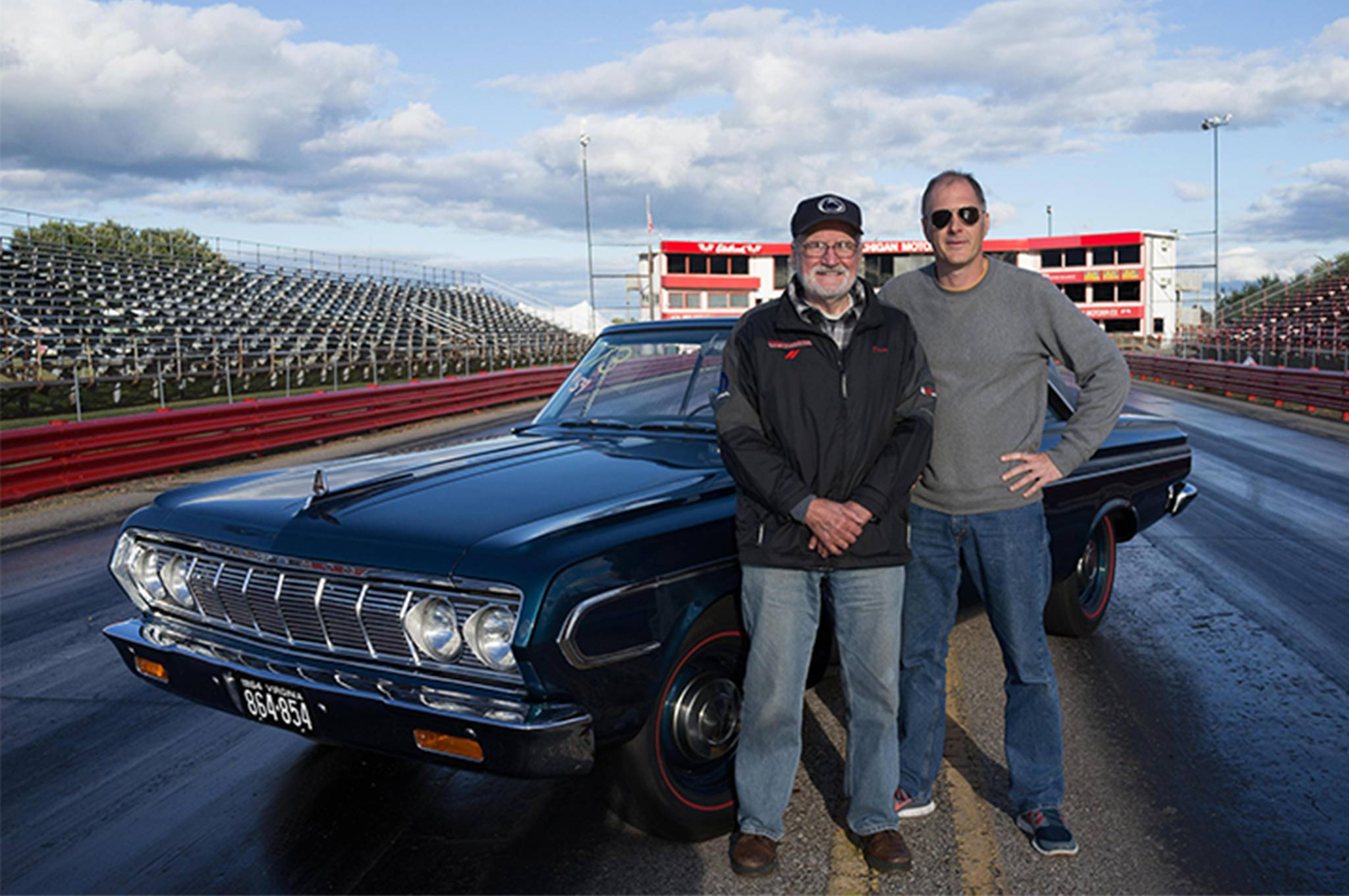"""Tom and son Tom S. with their more recent project, an all-steel, 11.0:1 compression Max Wedge 1964 Belvedere. With a pushbutton transmission and typical blueprinting, the car went 11.55 with a best speed of 122.56 mph against the Street Hemis at the Pure Stock drags in Stanton, Michigan. """"I enjoyed every minute of the project,"""" says Tom of the car he and his father raced. """"We approached the effort like we were preparing the Motown Missile. Every detail was evaluated one at a time at the racetrack. Results were corrected for weather. I became a better driver. The car went faster and faster. You can't beat the scientific method, baby!"""""""