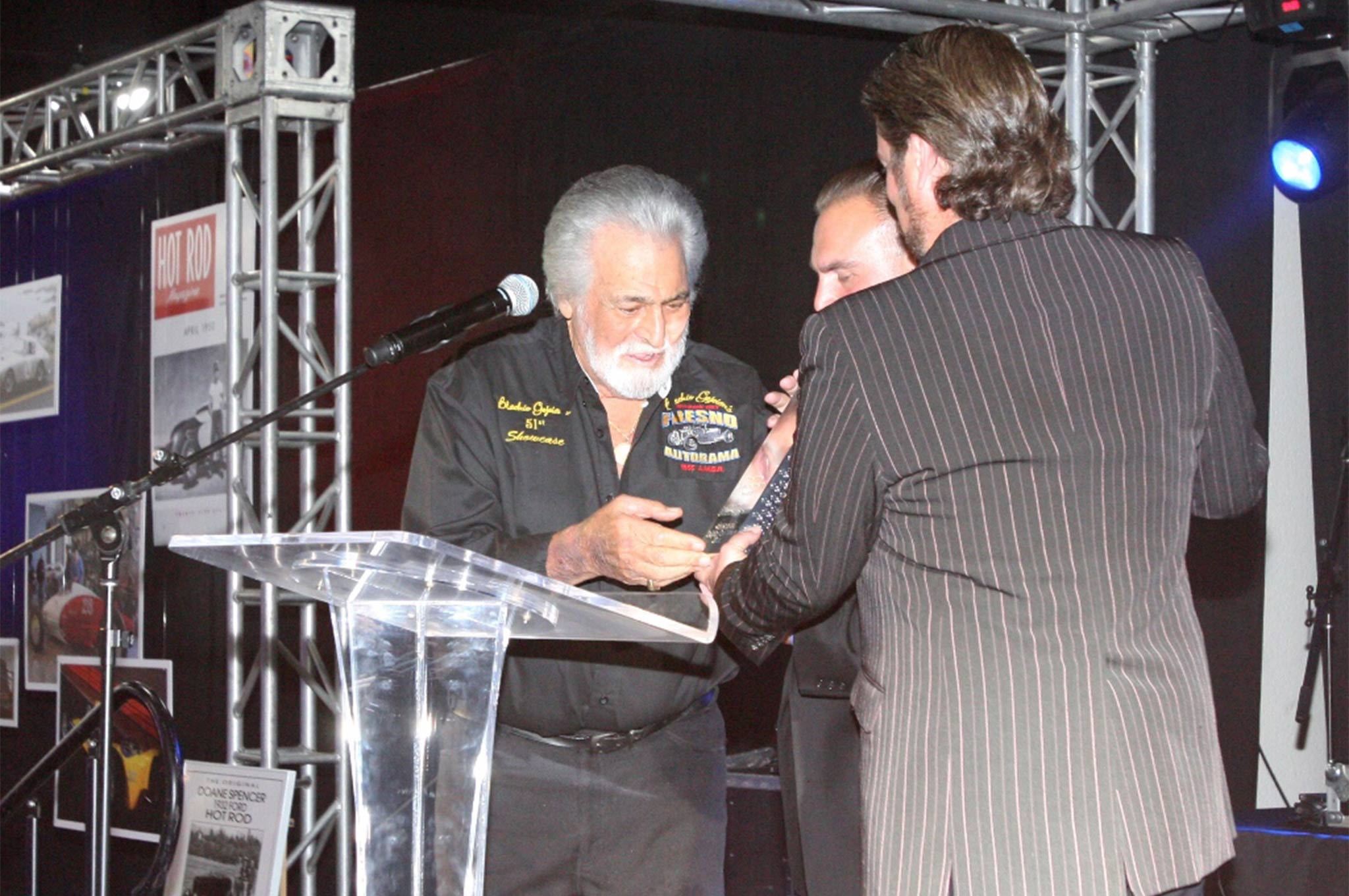 Blackie Gejeian receives his Lifetime Achievement Award from Dave Shuten and Beau Boeckmann at Galpin Auto Sports.