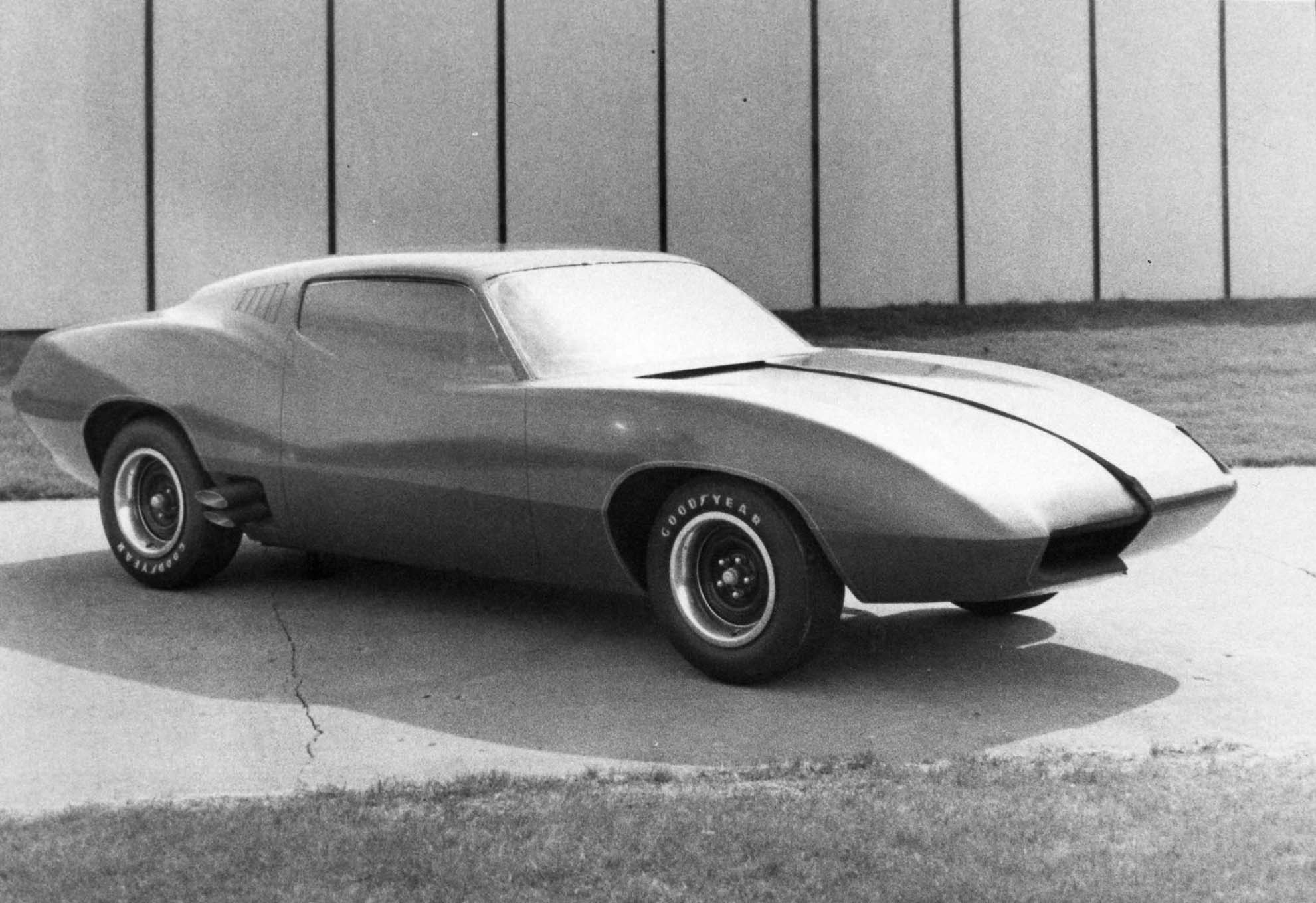 The Herlitz/Sampson clay, dated April 21, 1969, shows the fluid approach with extreme front overhang and aerodynamic nose. Hidden headlamps would have been incorporated into the front end. Notice the lack of a quarter window and exhaust tips incorporated into the rockers ahead of the rear wheel opening. The quarter panels ramped up and then dropped back down toward the rear backlight. The profile pulled down the green house and made the overall profile lower.