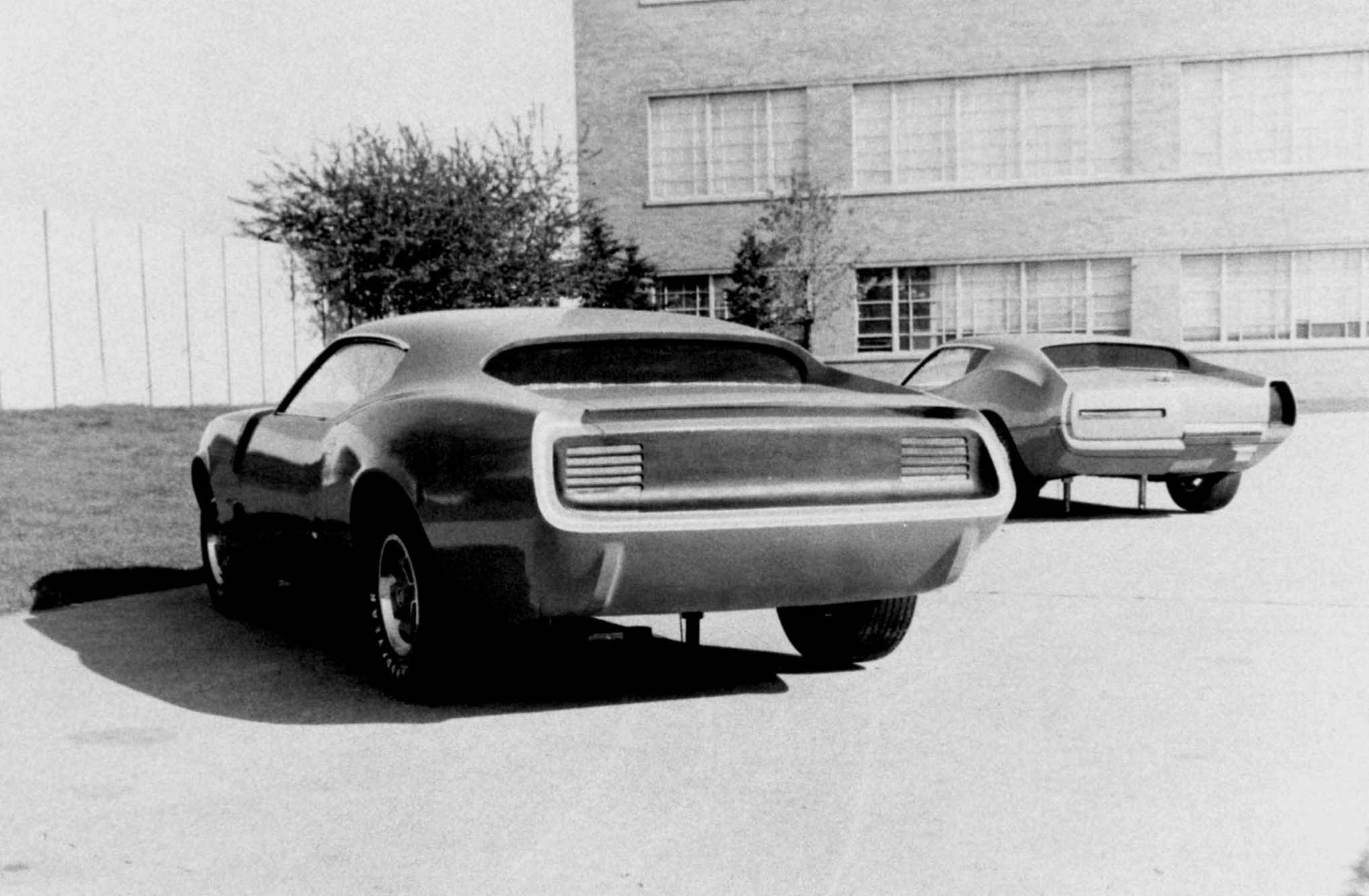 "Check out these two variations on the fourth-generation Barracuda theme. On the left is one of Matsurra's clays, with its deep-tunneled backlight that faired into quarters. The quarter panel ramps were similar to the 1970 - 1974 design. The spoiler was center mounted on the decklid and blended into the ends that were in line with the tops of the quarter panels. The tail lamp panel was recessed above what would have been a concealed rear bumper. On the right is Don Hood's ""Vestige"" clay with two different proposals for tail lamp and rear bumper configurations. Notice the extreme ramping over the rear wheel opening."