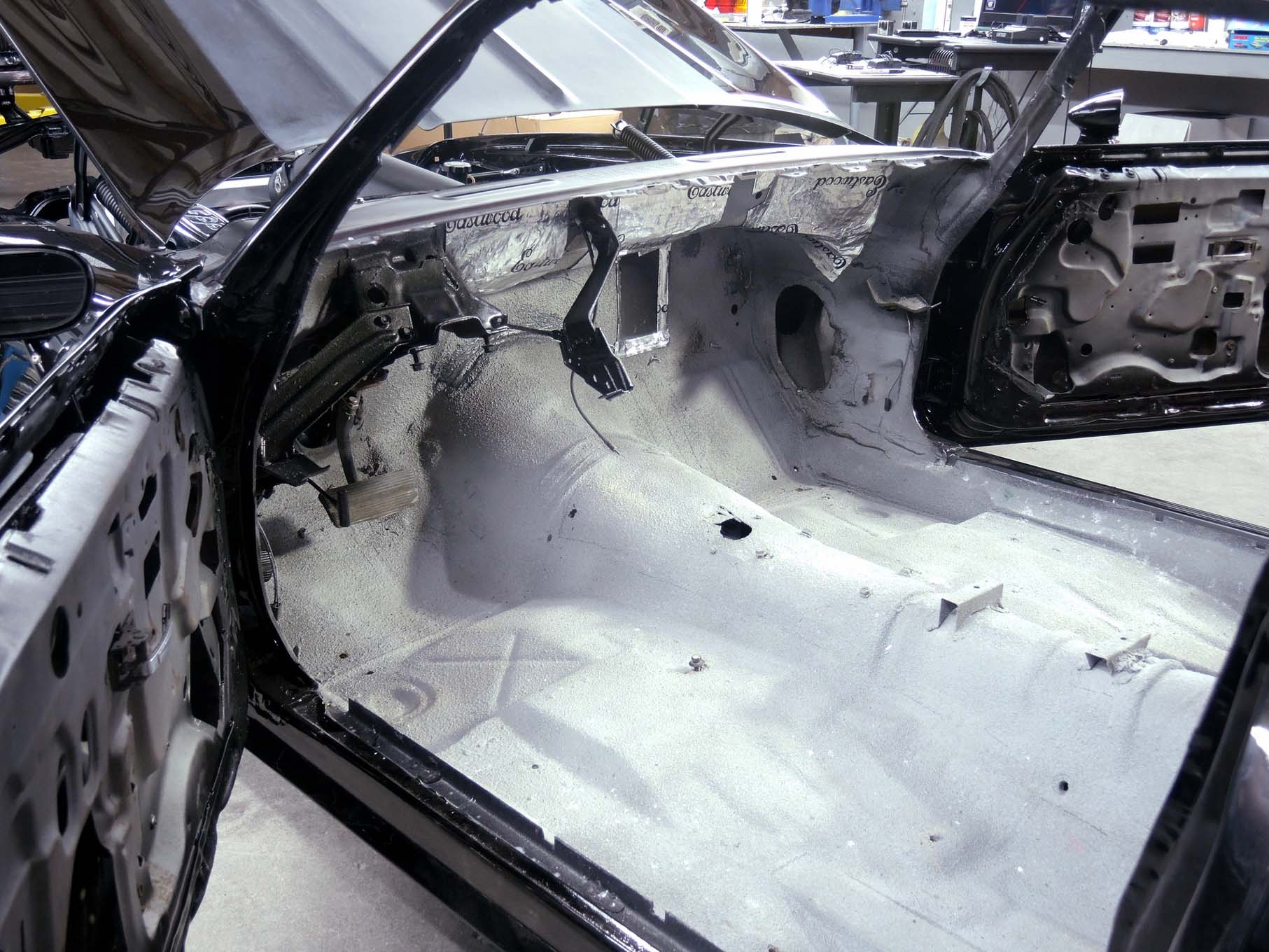 We are starting with a clean slate. The tub of our F-body is rust-free, empty, and sprayed down with Eastwood's thermal insulation coating, as well as peppered with a few insulation tiles to dampen the transfer of road noise and heat from the engine and exhaust.