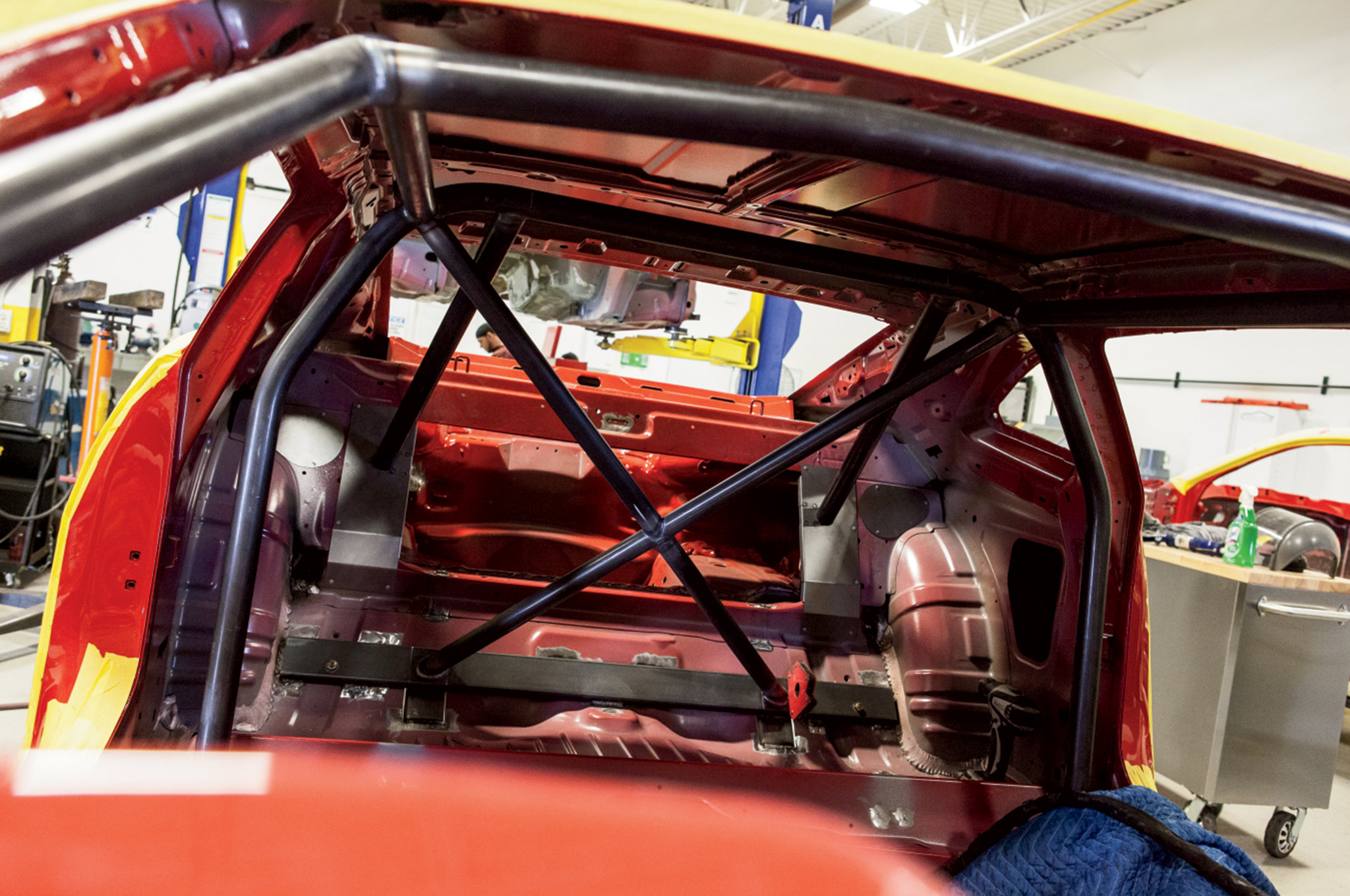 Here you can see the rear main hoop, front hoop, rear X, and rear down bars in place. Every weld is done by hand at the factory and inspected by both the COPO team and the NHRA prior to delivery. Note the laser cut rear down bar covers. A nice touch to cover the factory rear seat area.