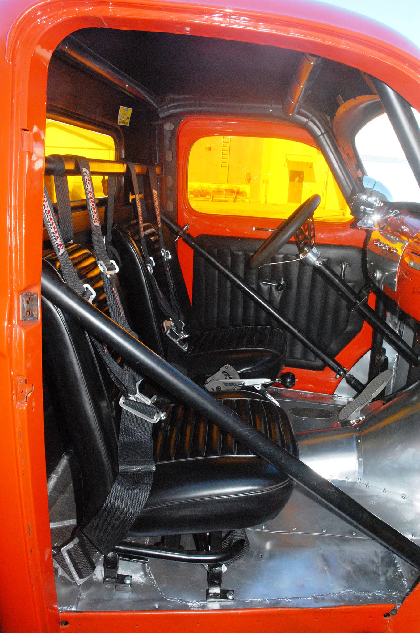 For being so cramped, it's amazingly comfortable inside. The Hairy Hauler is equipped with a six-point rollcage with swing-out driver-side bar, a pair of black vinyl seats, G-Force Racing Gear safety harnesses, Stewart Warner instruments, a Hurst Quarter Stick with Hurst Line Loc, orange Plexiglas windows, and aluminum interior paneling. The 'cage and tinwork were done by Jim Horvatis.
