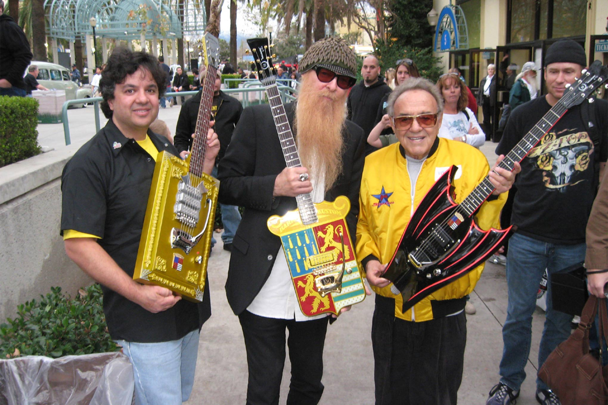Hallmark Guitars' Bob Shade, ZZ Top's Billy Gibbons, and George Barris pose with Shade's Barris-inspired guitars, the Dragula, Barris Krest, and Wing-Bat. Photo Credit: Michael G. Stewart