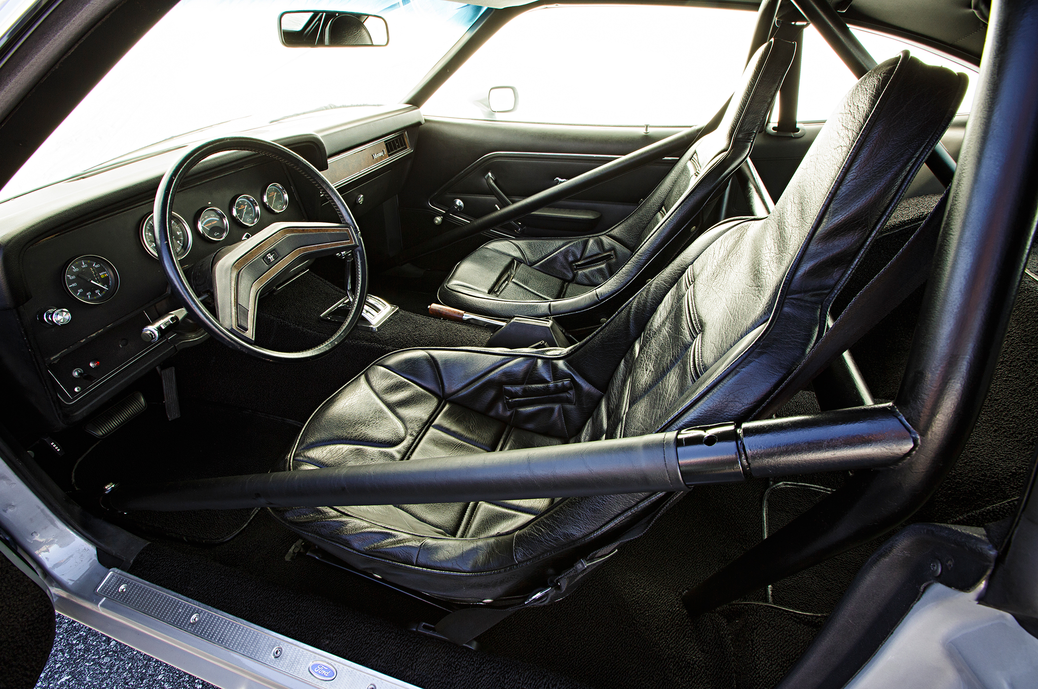 "The interior is completely original, other than carpet and headliner. The seat covers and Don Hardy Race Cars seats were G&R race pieces from their old Pro Stock cars. One of the original seats was shattered, so Tate had fiberglass support ""cups"" fabricated off the one good seat to support the bottoms and a metal plate on top of the broken seat formed the repair. He then injected marine expanding foam to provide internal support. Tate reports that the seat is now ""solid as a rock."""