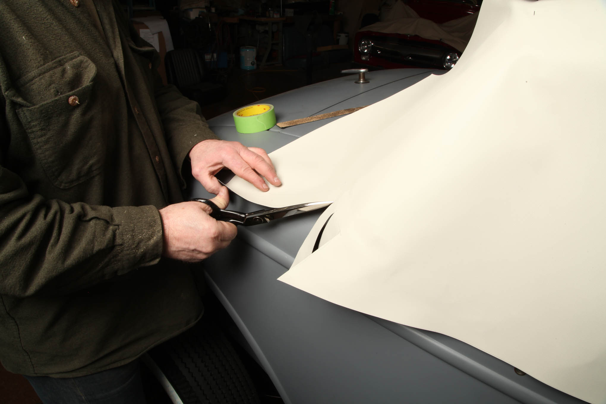 After stapling the side panels, Reichlin slit the overhanging vinyl to relieve the tension. The panel then splays out and lays flat around the sides.