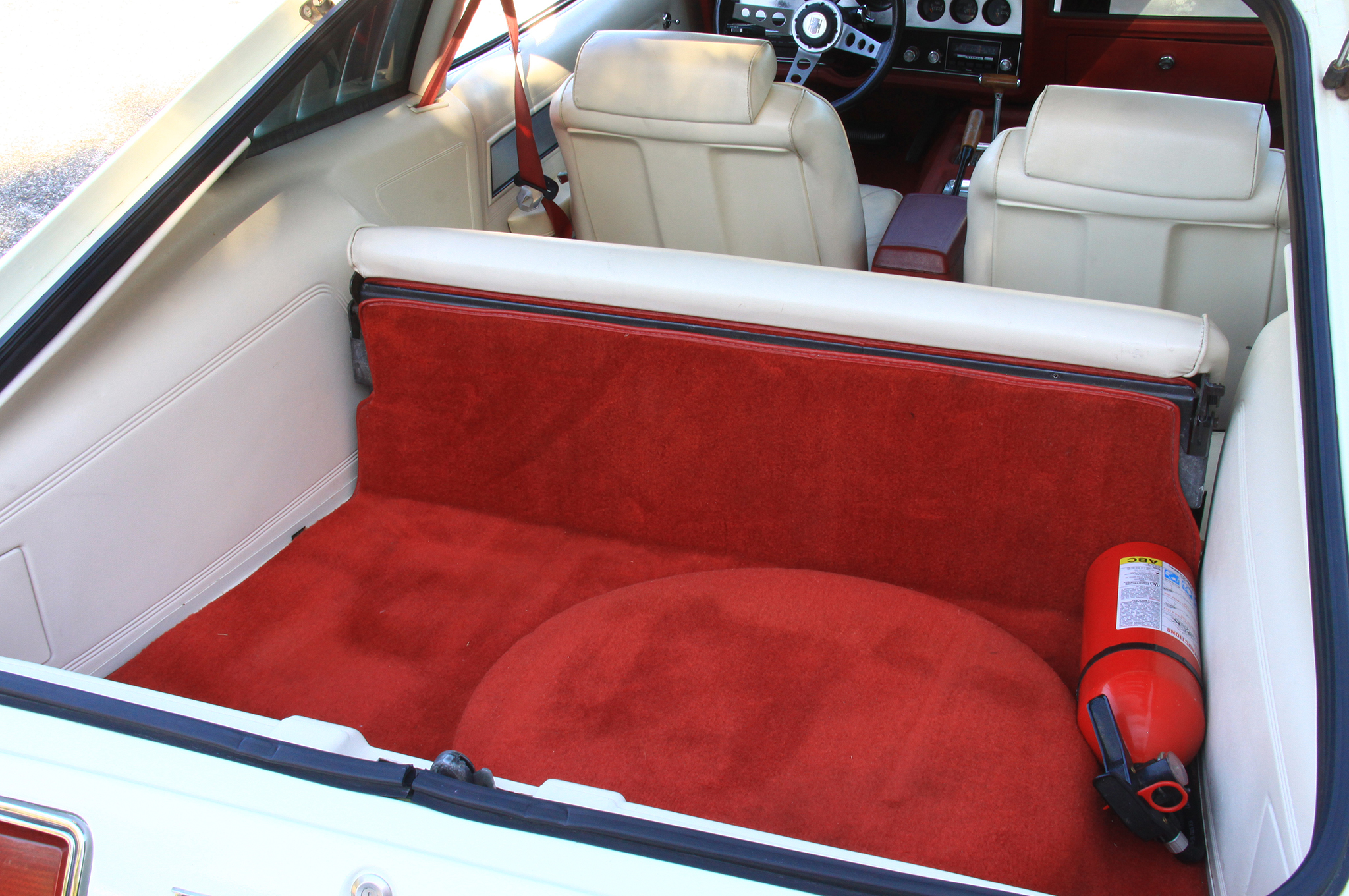 Check out this pristine fold-down rear seat area, which is factory. An abundance of towels and blankets protected it from the sun for nine years.