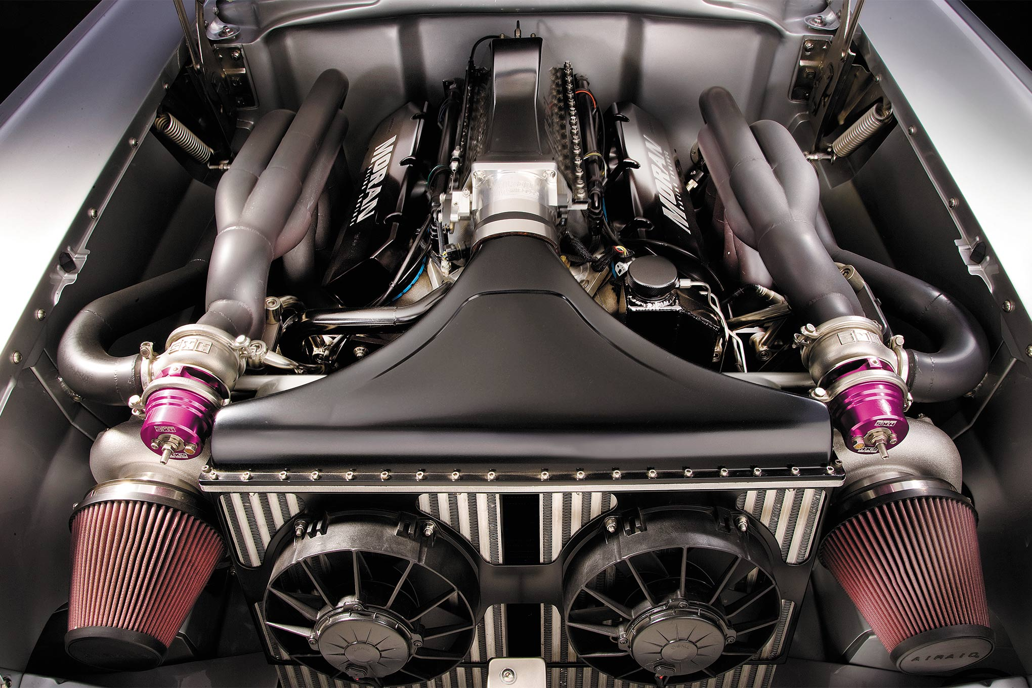 "From any angle this is an impressive and intimidating engine; a 540-inch Dart Big M steel block (Chevy), 80mm Precision turbos, and 60mm HKS wastegates. Did we mention 1,695 hp at 16 pounds of boost at 6,500 rpm? Can you say traction control! Look and enjoy: the headers, and the remainder of the exhaust system, were masterfully built by the crew  at Dominator Street Rods. There are no mufflers! Heat is horsepower and this big-block is plenty hot, requiring the use of a Meziere electric water pump and a pair of SPAL electric fans matched to the Steve Long brass radiator. Additional cooling is required and aptly handled by two more SPAL fans hidden in the front fender area that evacuates air from the engine compartment. Should Red Line want to dial back the horsepower by ""only"" 10 pounds of boost, the V-8 will produce 1,225 hp on 93 octane."