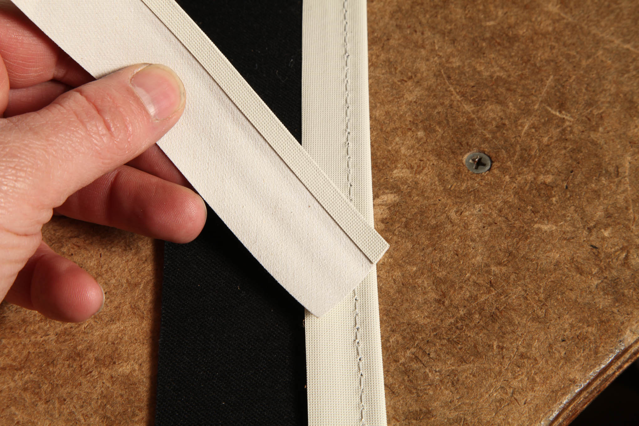 Reichlin finished the top and flap's edges with 1-1/4-inch one-edge turned binding strip. It simply wraps around the edge so the folded edge faces outward and then gets sewn along that edge. The black panel is the backside of the rear flap.