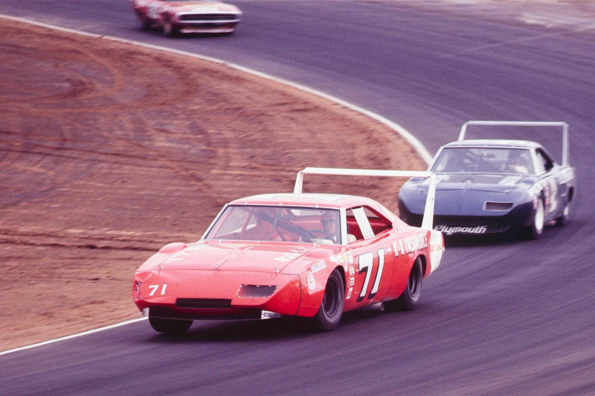 Isaac being chewed from the rear by Dan Gurney in the Petty Enterprises No. 43 Plymouth Superbird at the 1971 Motor Trend 500 at Riverside. Note the damaged front end on Isaac's Daytona.