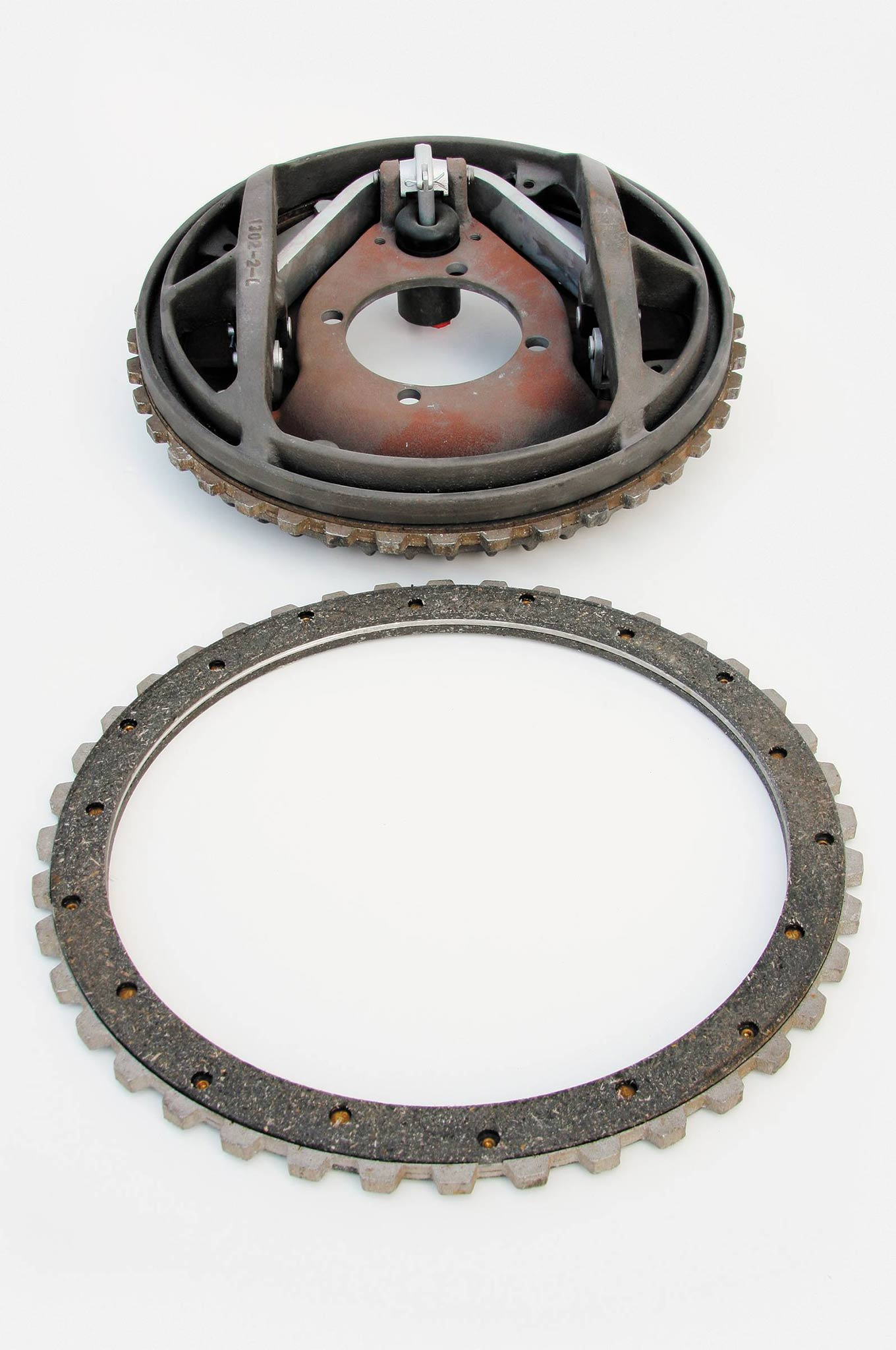 """The friction pad (lower part of the photo) runs completely around the magnesium disc on both sides. There's twice as much brake lining here than on conventional Ford hydraulic brake shoes of the period, for 360-degree contact, and there are no gaps, so when they're properly adjusted, the Kinmonts don't """"grab."""" The original lining was an asbestos composite material. Re-liners today use a modern friction material."""