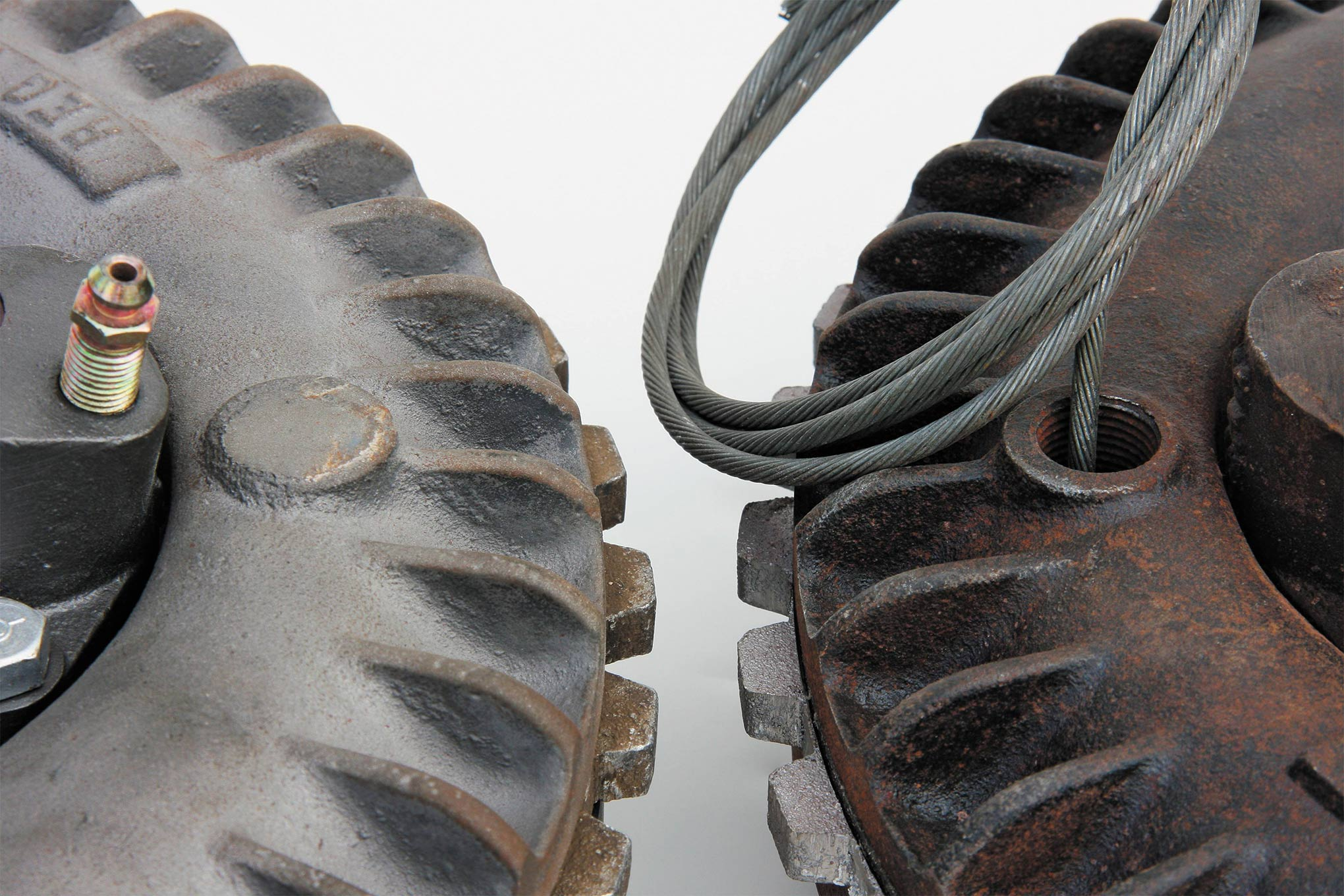 """Front and rear backing plates differ front to back and side to side. This rear hub (right) has a hole drilled for the emergency brake cable. Conventional Ford rubber """"boots"""" (not shown) are used to protect the brake cable and keep water from entering the brake assembly."""