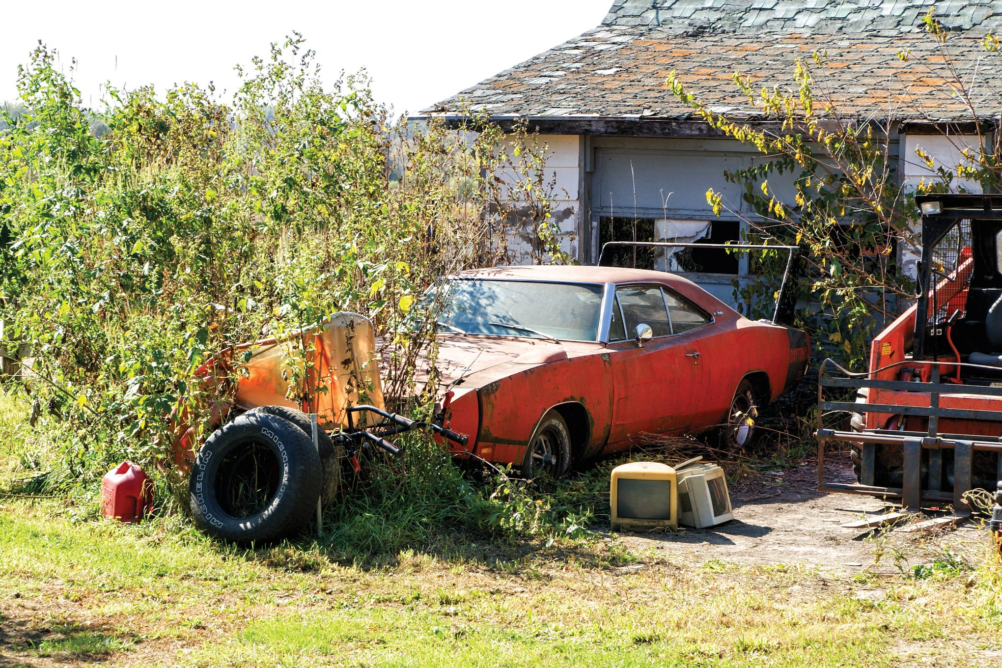 During the last three years, the weeds around this 440ci Daytona have grown and a skid-steer loader has replaced the car parked next to it.