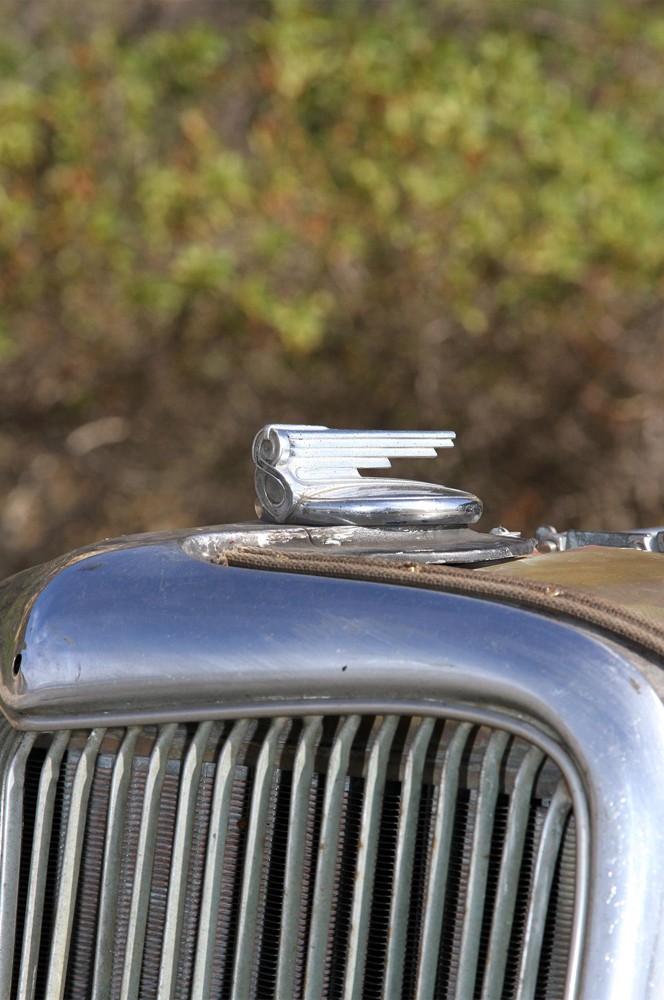 """The radiator cap atop the original '34 Ford grille shell is from a '30 Buick. Aaron chose the cap because of the """"8"""" in its design. It goes hand-in-hand with the Cadillac V-8 in the hot rod."""