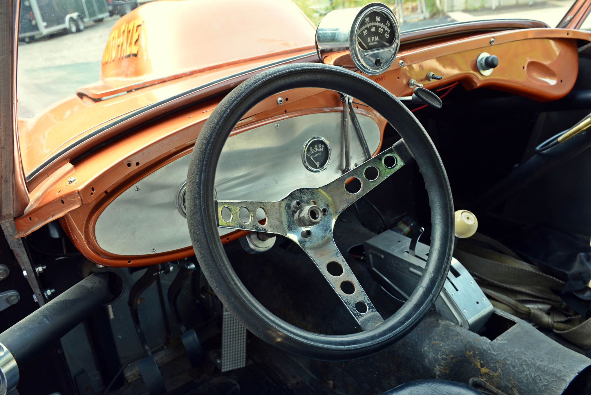 The Healy's interior is Spartan: seat, Superior steering wheel, and B&M ratchet shifter. A vintage Sun tach sits where it did 45 years ago. Notice the wrenches for adjusting the valves.