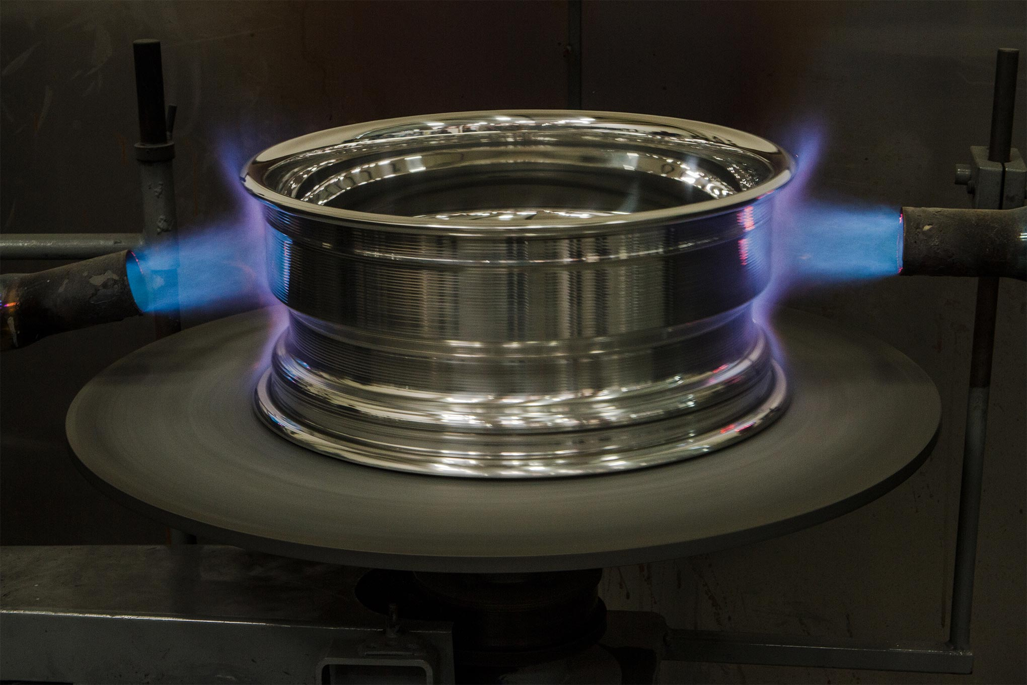 Once again, heat is used to expand the forged rim's shell as it rotates on this fixture.
