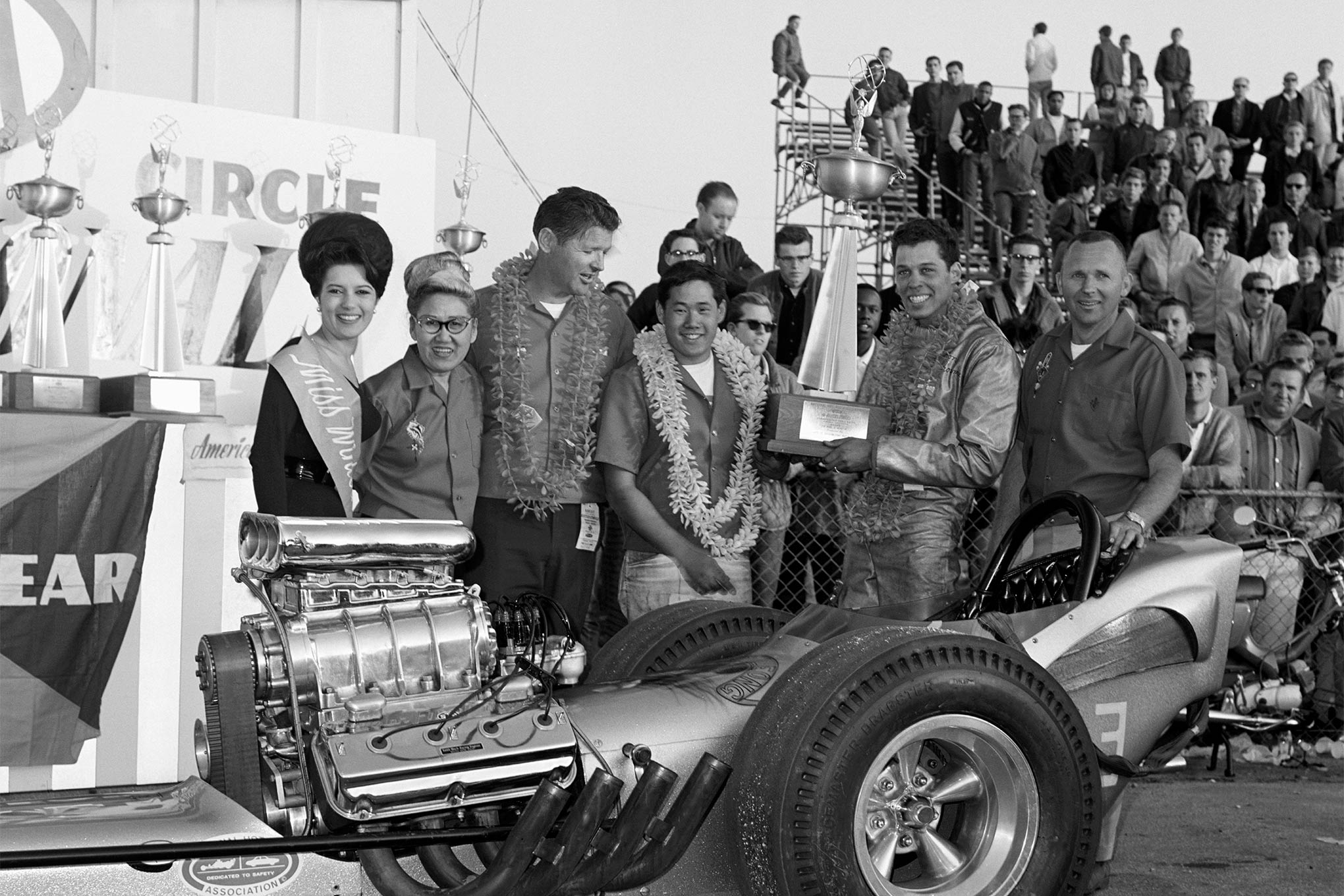The 1965 NHRA Winternationals winners from left Miss Winternationals, Roland's mother Teddy, engine builder Keith Black, Leong, Prudhomme, and crewmember Wes Hanson.