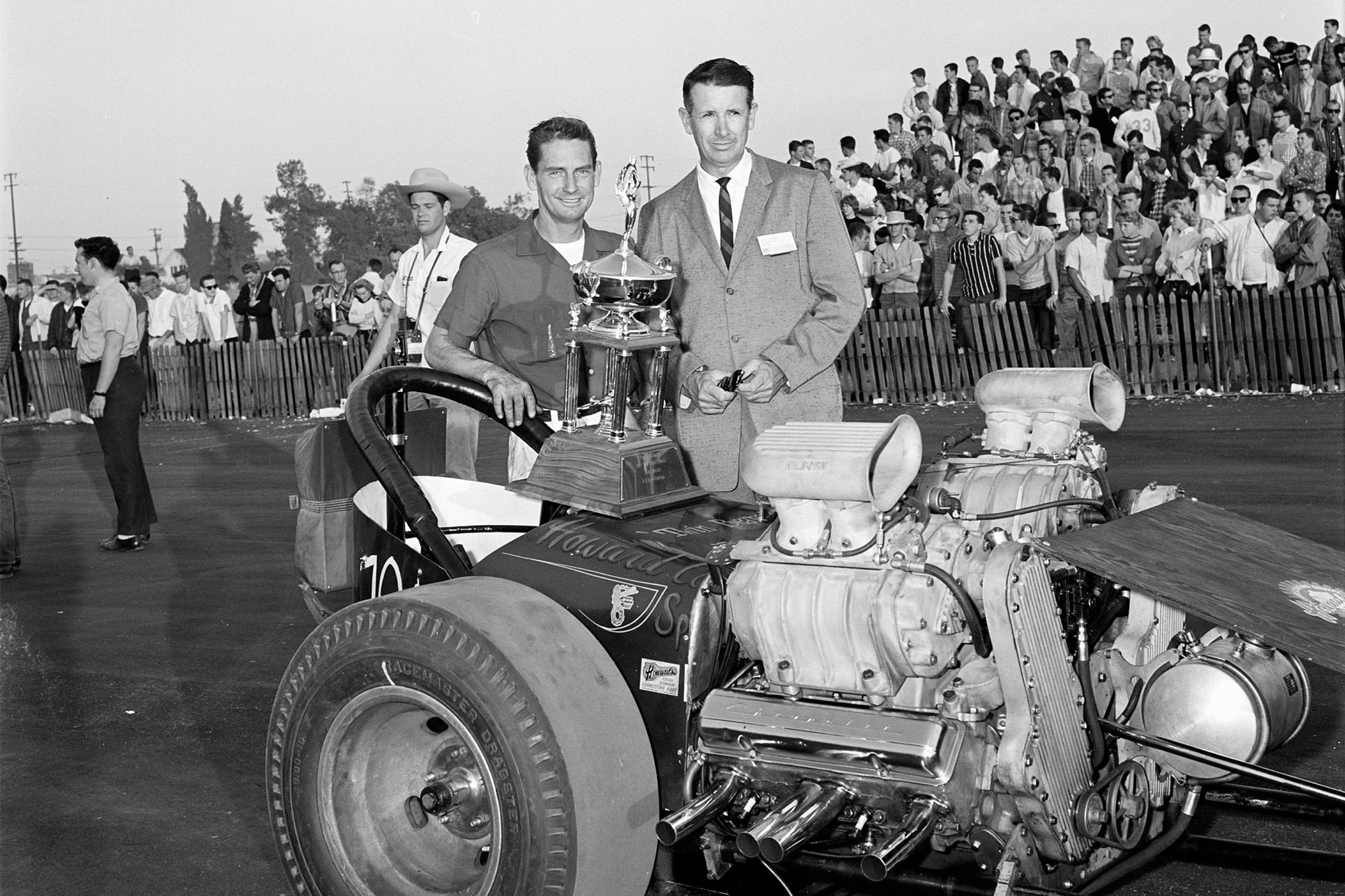 Top Eliminator honors went to Jack Chrisman and the Howard Cams Special with its plywood aerodynamics and twin-Olds power featuring new roller cams. Tuning was 16-year-old Jerry Johannson. This is Chrisman getting the trophy from NHRA President Wally Parks, with HOT ROD's Tex Smith in the cowboy hat just to the left.