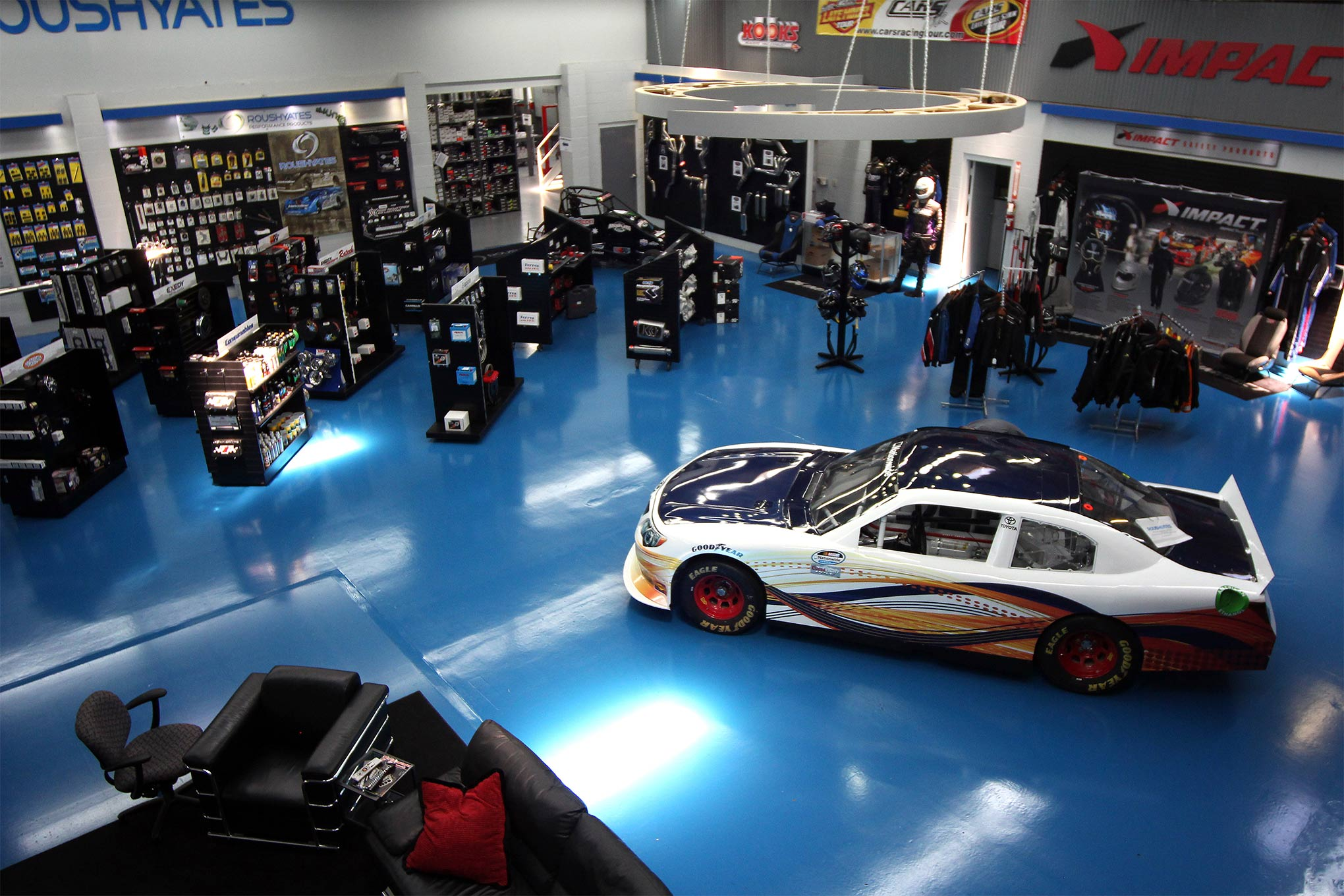 Roush Yates Performance Parts' main showroom is filled with racecars and displays for the new parts the company carries, but just beyond that doorway in the top of the frame is racer nirvana--several thousand square feet of lightly used parts off of NASCAR Cup cars that you can purchase for a fraction of the new price.