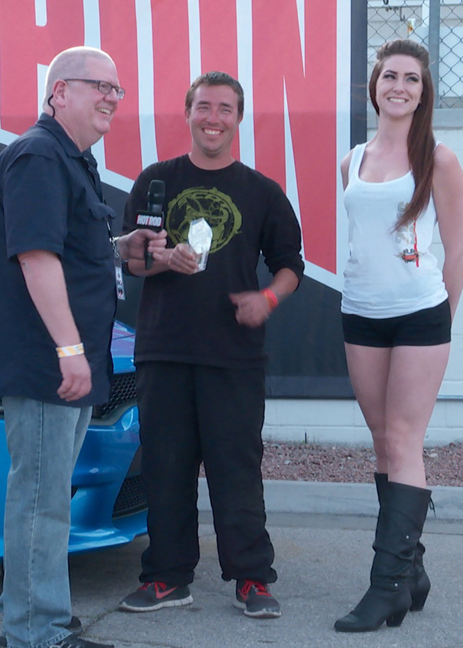 Editor Johnny Hunkins and trophy girl Blythe present David Boyer with his crystal Scat Pack Challenge trophy in the winner's circle.