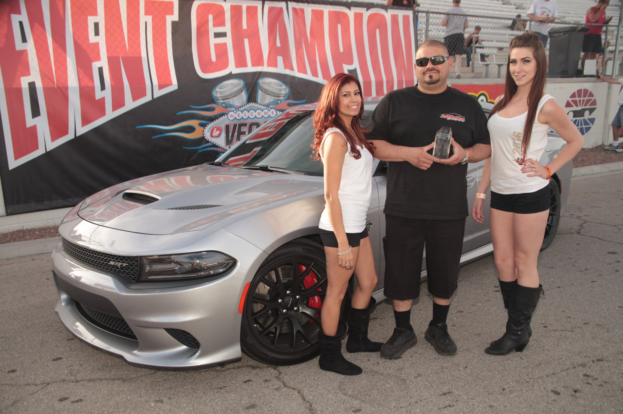 Trophy girls Jennifer and Blythe present winner Al Jimenez with the 2016 Mopar Muscle Hellcat Challenge trophy in the Las Vegas winner's circle. Think you can build a faster Hellcat or drive it better than Al? He says he'll be glad to take you on next year! Same place, same time.