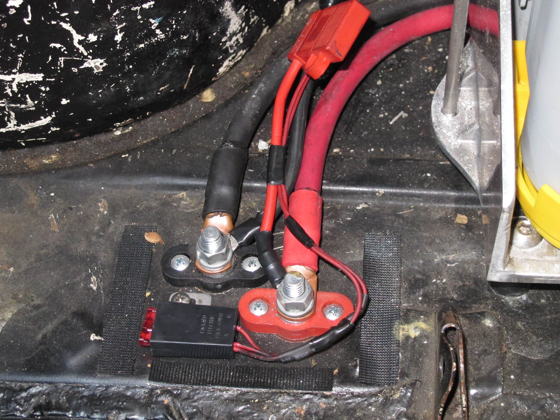 Bulkhead terminals were used to connect the battery to the cables leading to the front of the car. Note the fuses for items that require constant battery power