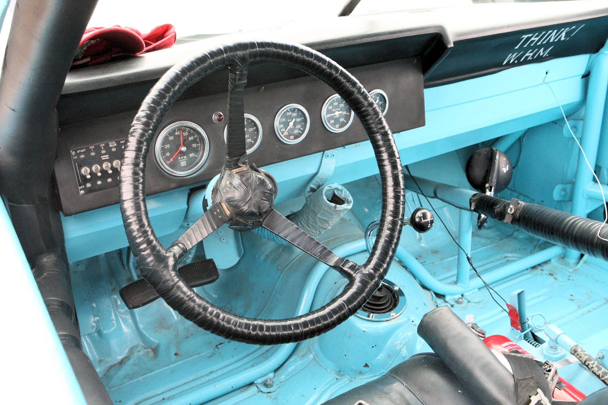 The driving compartment of a pretty simple 1960's era Stock Car. Notice the steering wheel and roll bar padding.