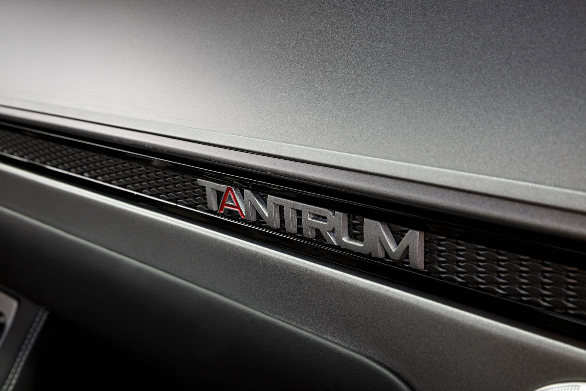 The Tantrum emblem in the dash mirrors the black and silver tone of the car, with just a hint of red highlight.