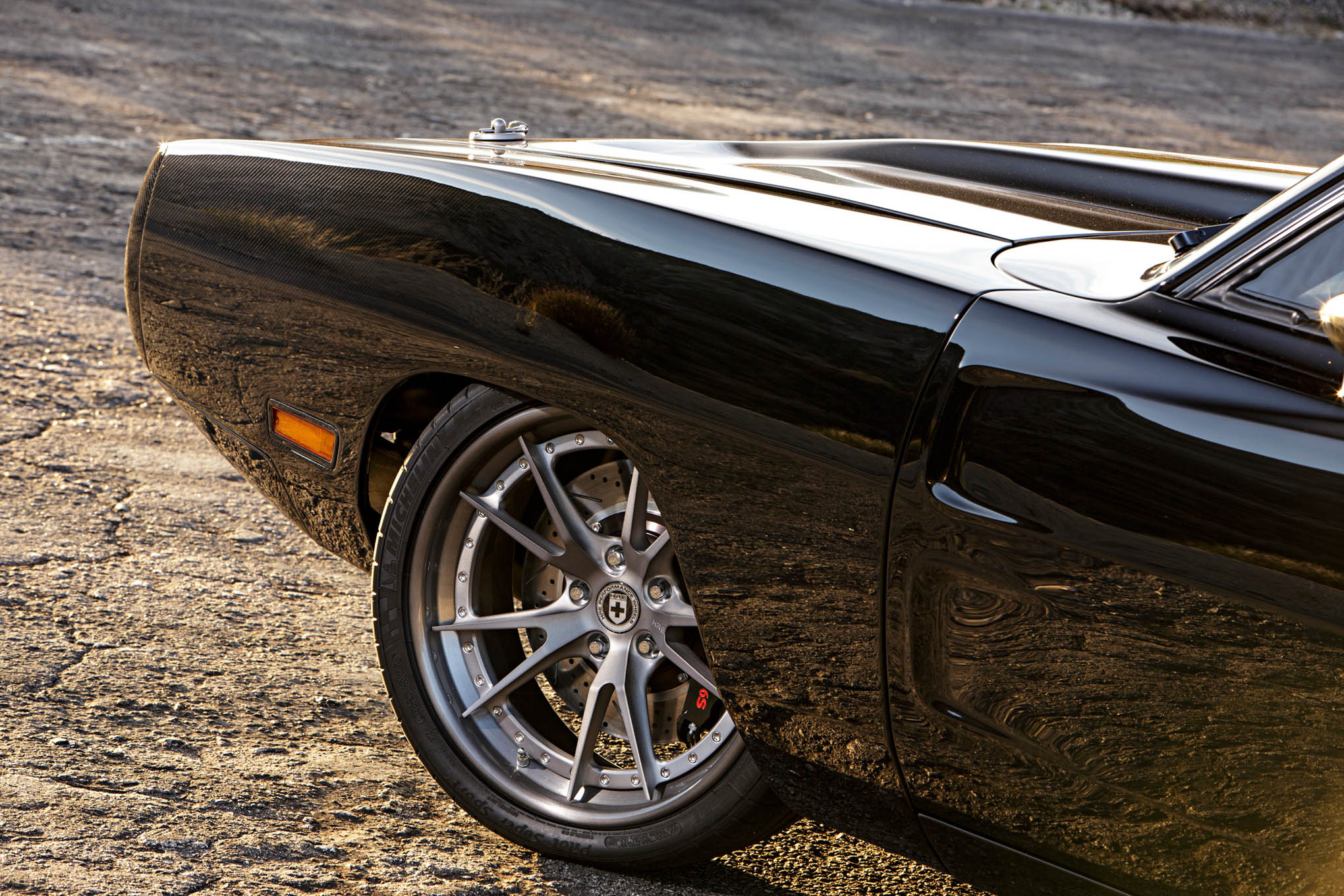 Black paint fades to a clearcoat to expose the carbon-fiber front fenders and hood.