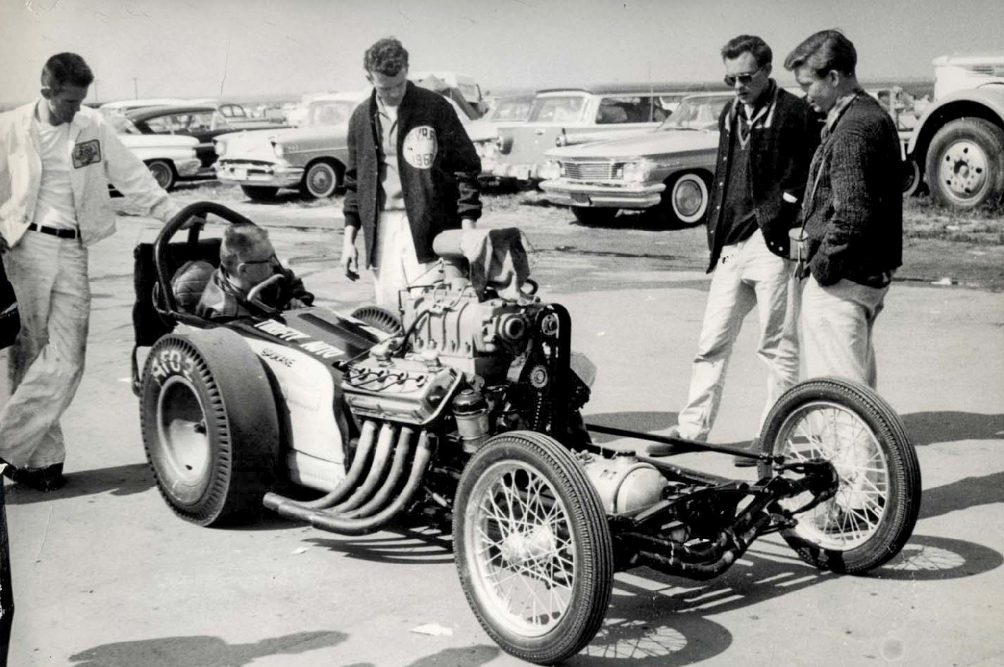 Here's another photo from the March Meet. By then the crew went high-tech with a lead-filled tube bolted to the front axle. Stortroen is apparently doing something under the cowl, perhaps fiddling with a bottle valve? Leaning on the rollbar is belly-tank pilot Charlie Markley. That's Lew Shaw immediately to Don's right.