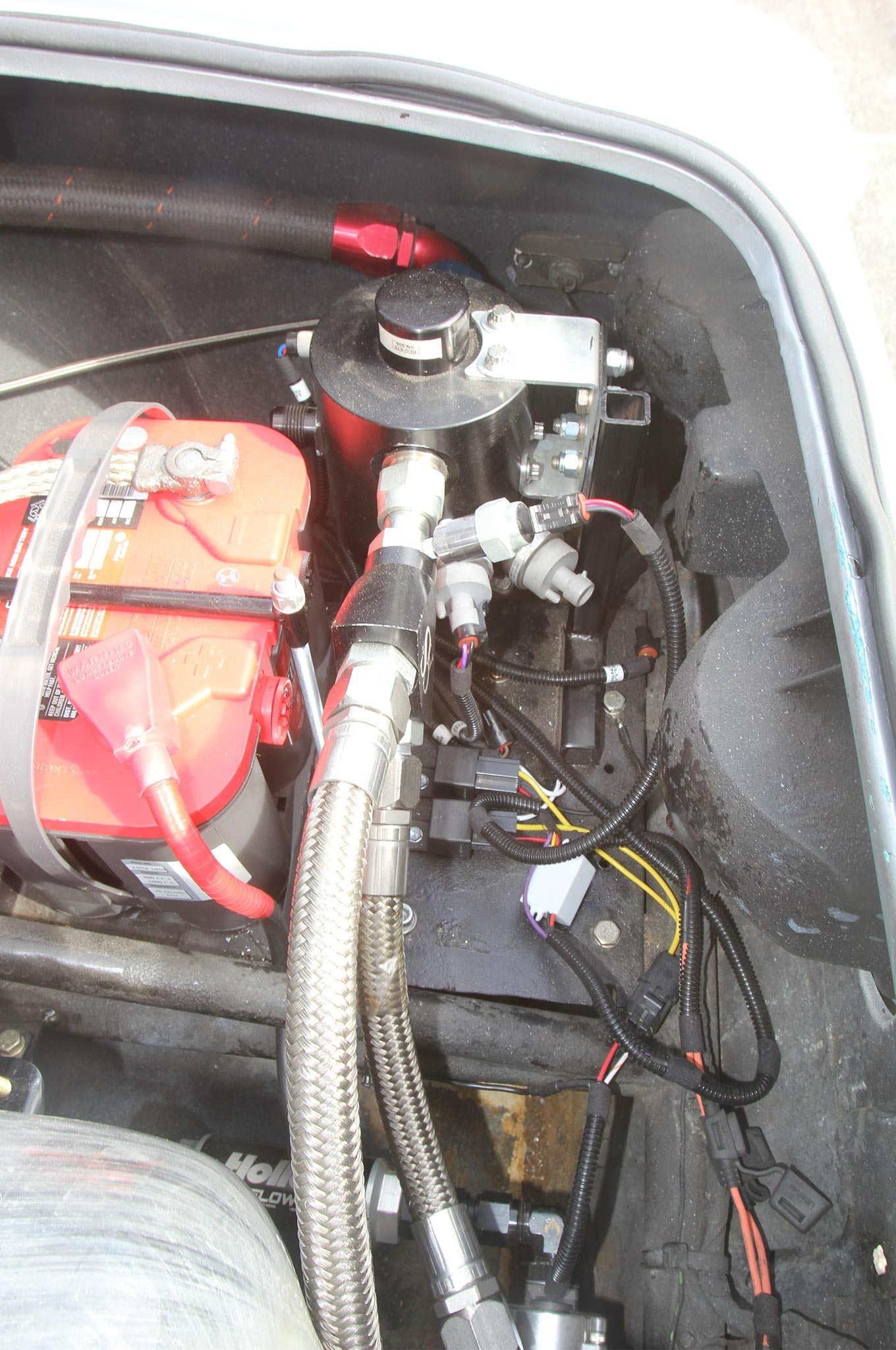 The two high-pressure lines Y into the pressure regulator and then a single, large -20 AN line leads through the interior to the engine bay.