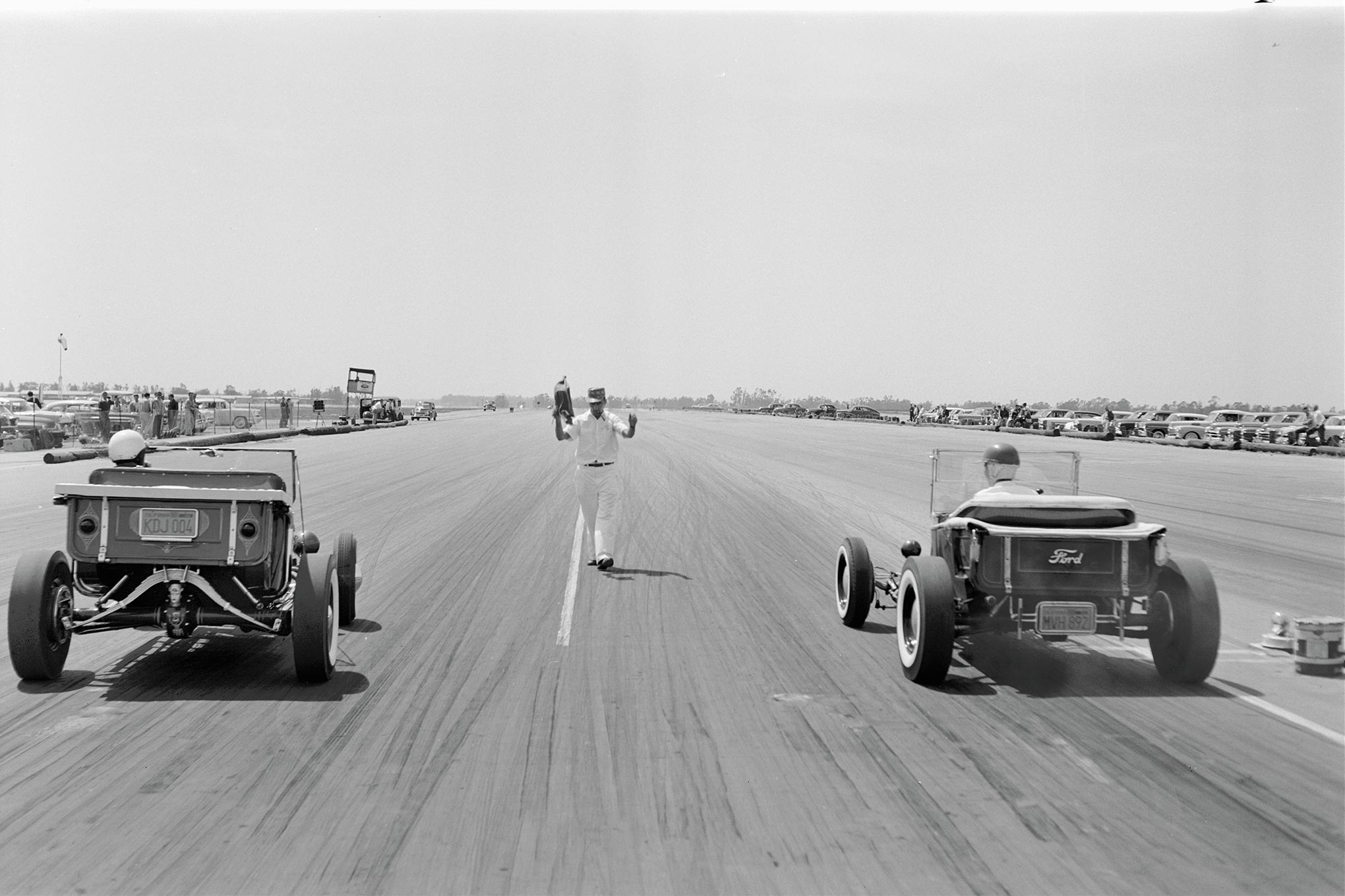 """The world's first and second T-buckets met only this one time, at Santa Ana in March. We thought we'd seen every photo of the grudge match until this Wally Parks negative surfaced in the PPC archive. C.J. """"Pappy"""" Hart flagged off a battle won by Ivo (right), though Grabowski arguably won the war when a Life magazine team followed him—not TV Tommy—to Bob's Big Boy drive-in to shoot the famous full-page photo of Norm chewing on grilled cheese. (See Apr. 20, '57, Life, """"The Drag Racing Game""""; June '57 HRM, """"Life at the Drags."""")"""
