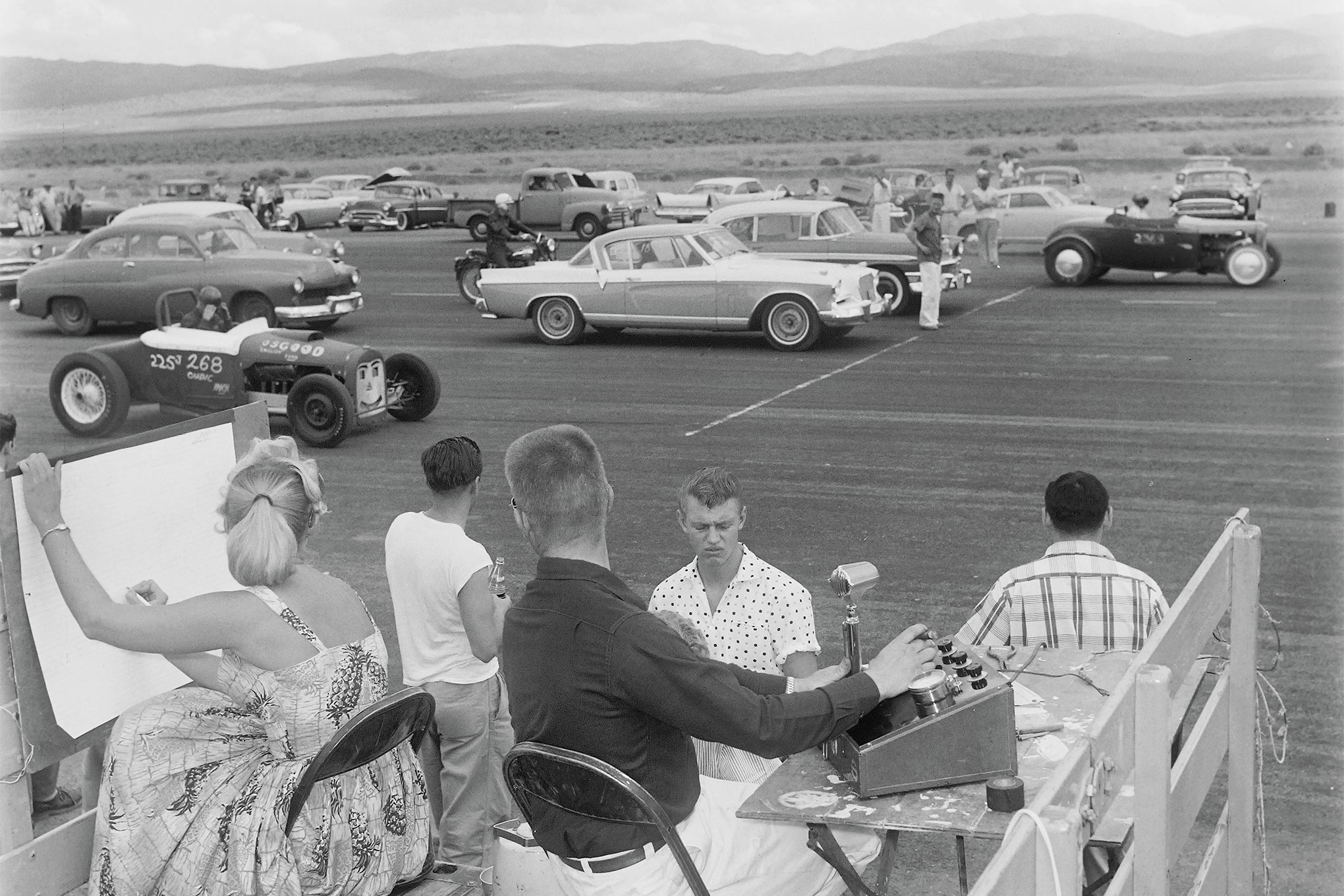 Two published frames from the same angle and roll of Eric Rickman film afford better views of announcer-timer Bob Fabel and scorer-trophy queen Sylvia Fore (Dec. '57 HRM; Nov. '11 HRD), but this outtake has the best background. Half-mile, four-car drags were easily accommodated by the 8,000-foot-long Douglas-Tahoe Airport runway in Minden, Nevada. Racers loved the extra quarter-mile to build respectable speed at 4,700 feet above sea level.