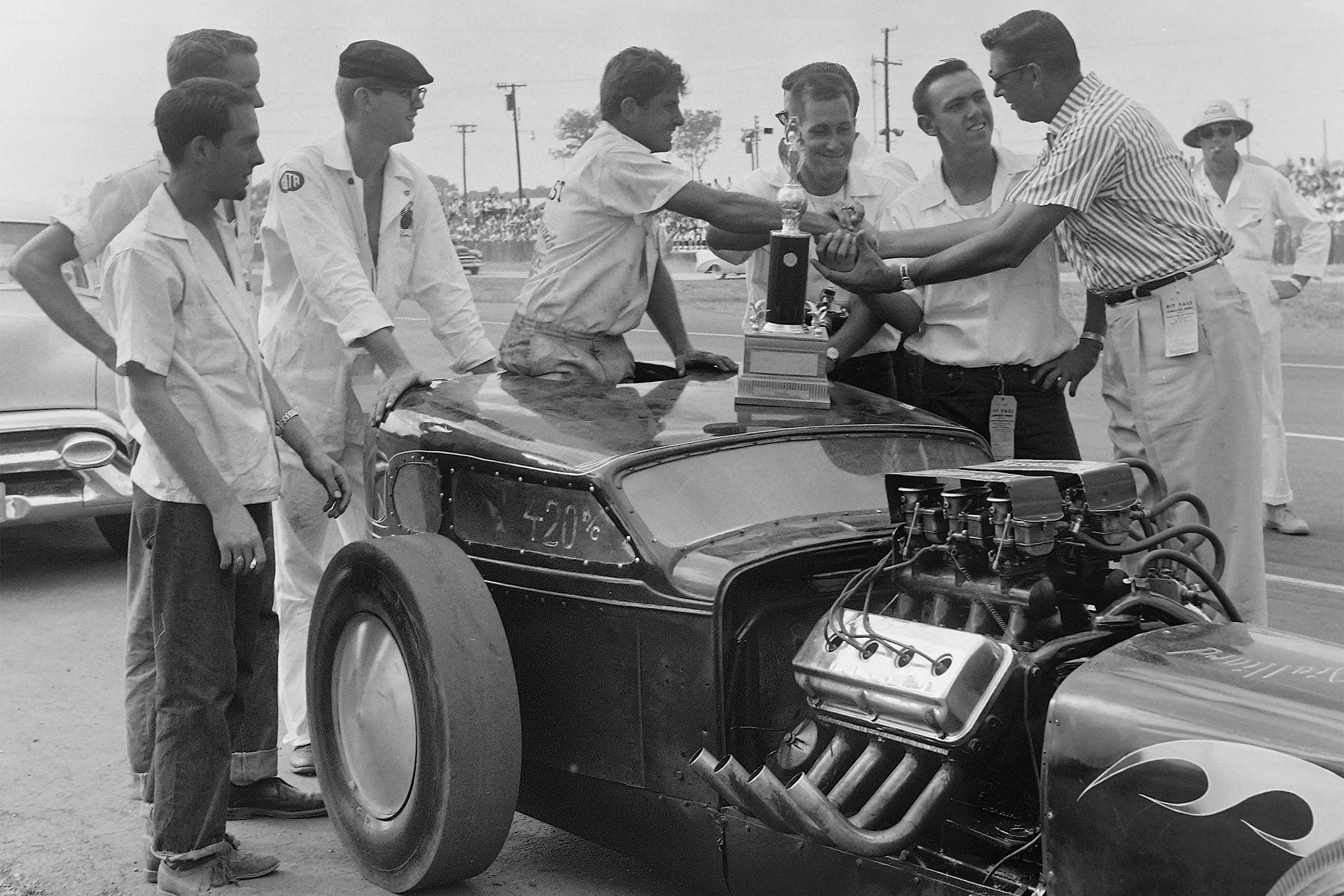 Wally's presidential duties included personally presenting awards. The A/Competition Coupe/Sedan trophy was claimed by Lee Roy Mackey, whose near-perfect Nationals further included an NHRA speed record (119.68) and runnerup Top Eliminator finish. Note the early zoomie headers, seven full seasons before becoming fashionable for Chryslers.