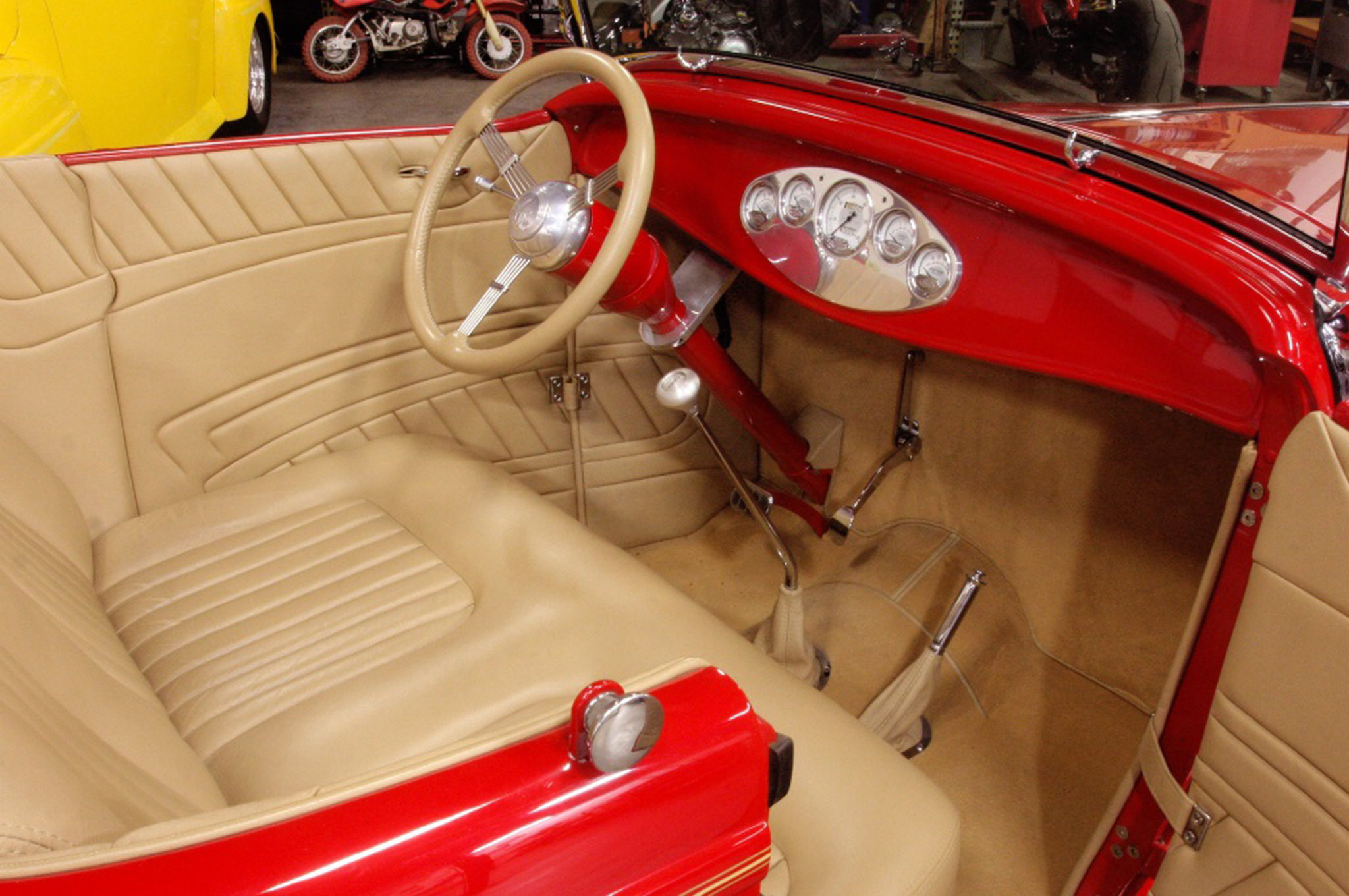 The interior was built by Ron Mangus. Custom door panels and a Glide Engineering seat were upholstered in tan leather with matching wool carpet covering the floor.