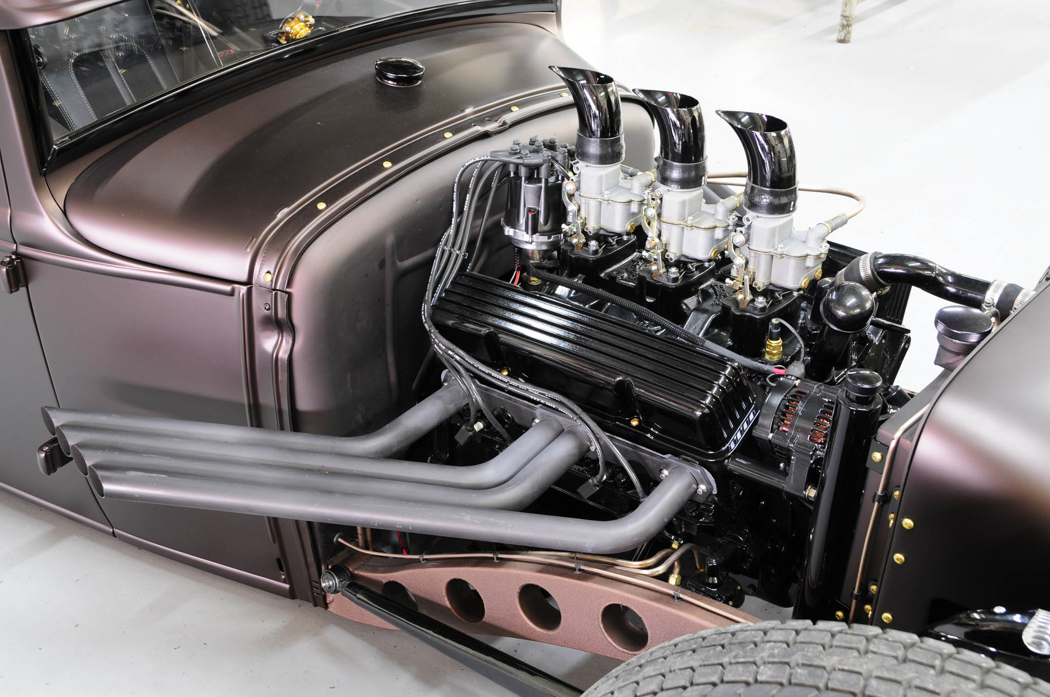 For power a 350ci Chevy small-block was coated in black and topped with an Edelbrock three-deuce intake wearing Stromberg 97 carbs. Attention to detail includes black finned aluminum valve covers, custom air cleaners and expertly laid out brass lines and mounting hardware.