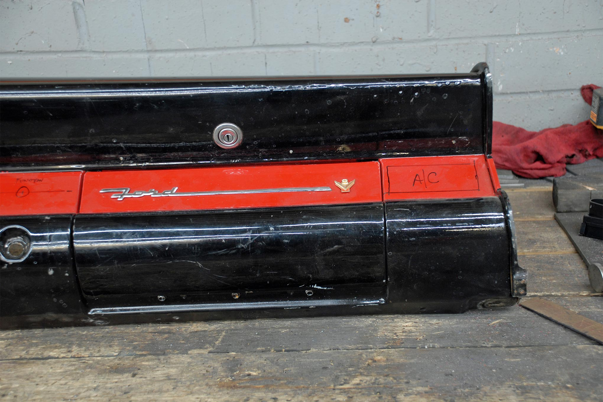 An A/C vent in each corner is an ideal location as automotive A/C works best if it can be directed on the occupants. The stock 1956 Ford glovebox door emblem is simply too cool to remove, a new one was sourced through Dennis Carpenter Ford Restoration Parts.