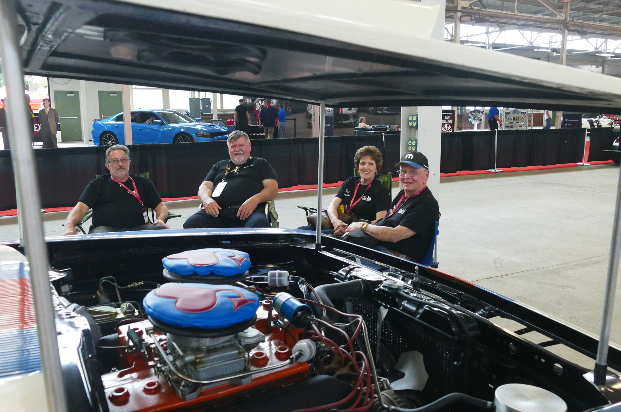 Don Grotheer (right), his wife Joann, owner Chuck Smith, and a friend sit in the staging area on Saturday. The engine in Grotheer's 1968 Barracuda is visible in the foreground.