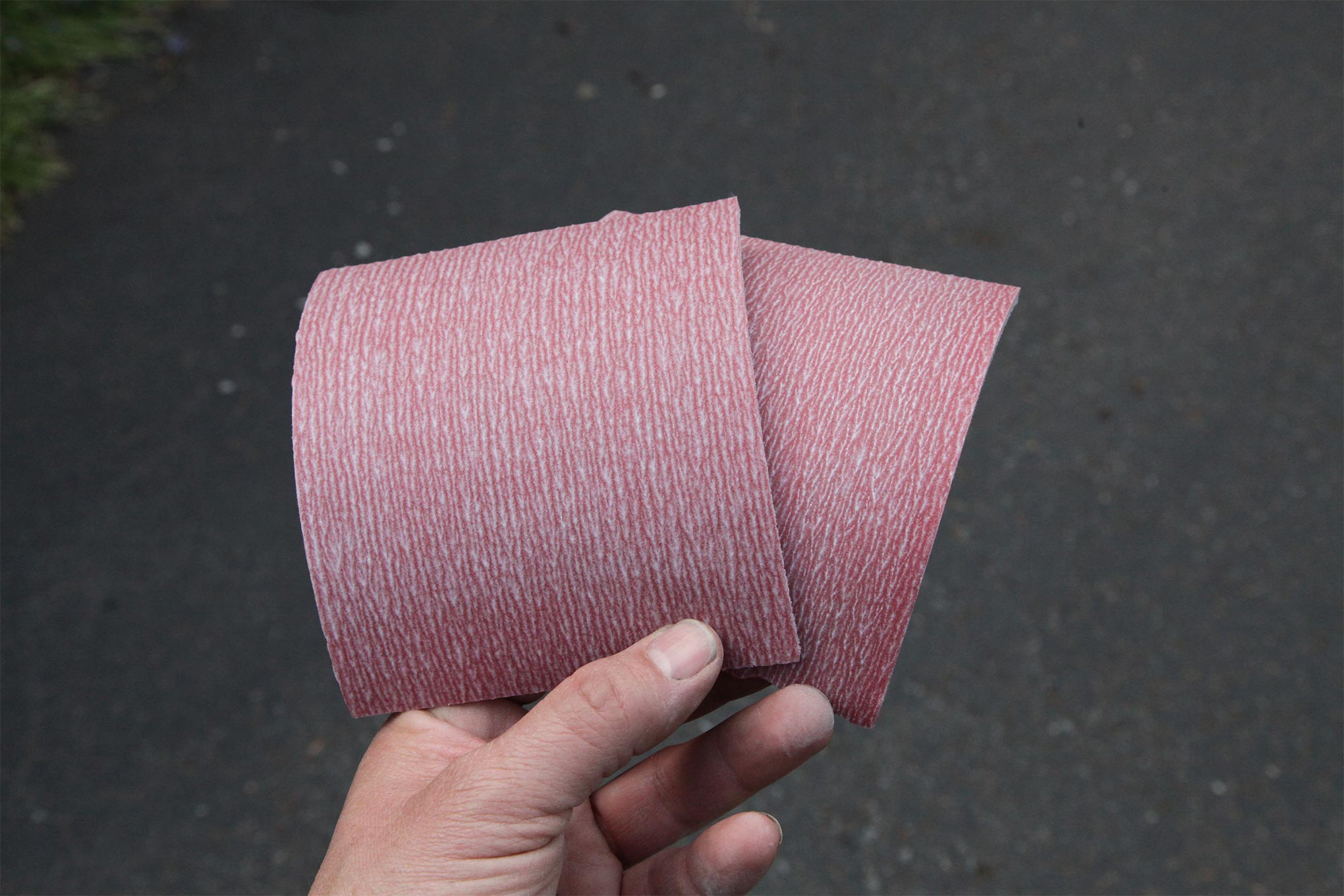 They appear the same but these two sanding pads are anything but: the one to the left has a 600-grit surface and the one on the right, 800. These finer grits are a consequence of the increased coverage capacity, which the manufacturers exploited to reduce material content, and by extension VOCs. Clint recommends going as fine as 1,200 for very-fine metallic finishes to prevent the metallic elements from orienting in the sandpaper scratches.