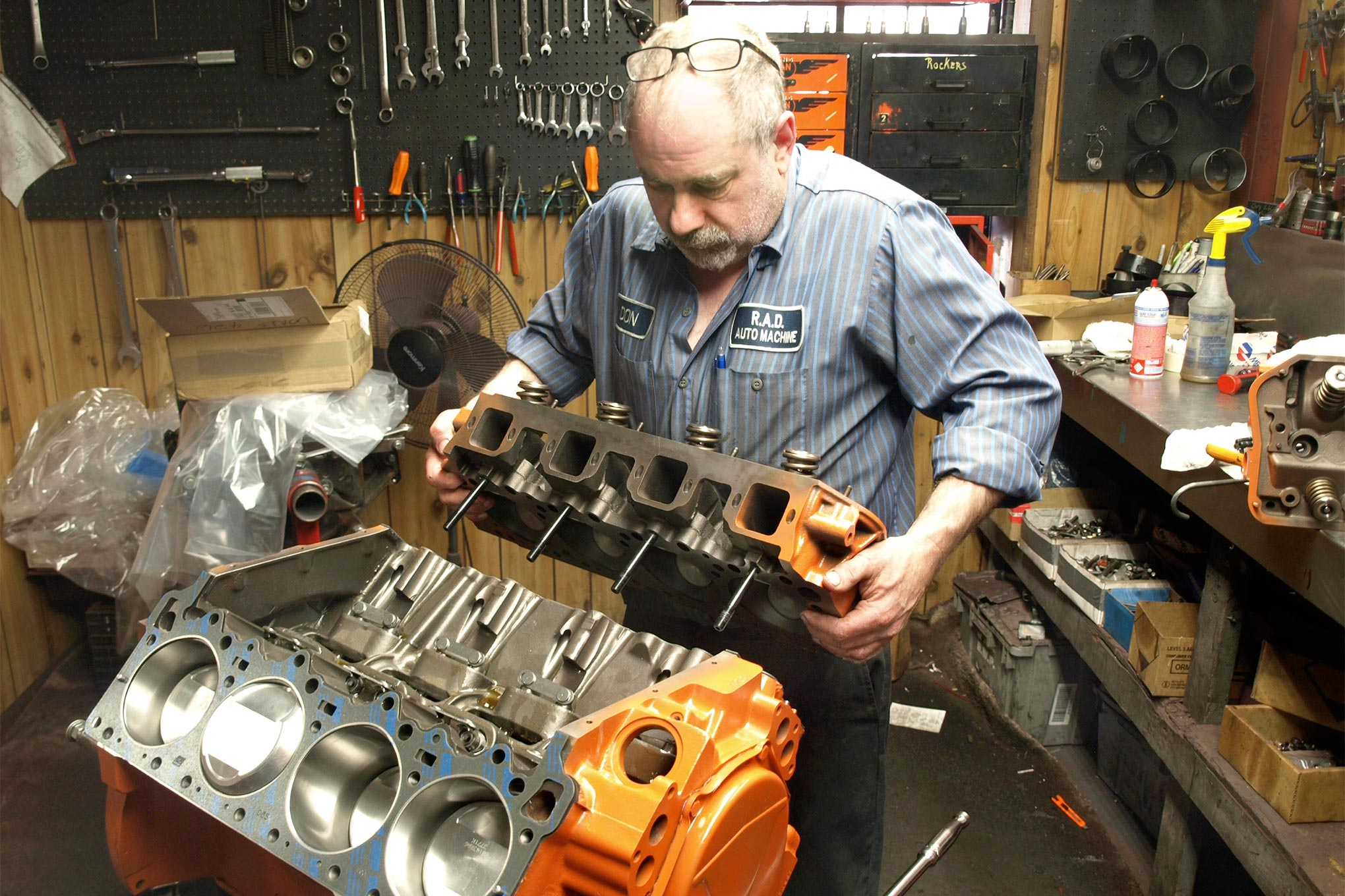 With the deck studs in place, Donnie sets the heads onto the block. Note the protruding piston dome on cylinder No. 6. Head gaskets are Fel-Pro (PN 1106) with a 0.039-inch compressed height. Not shown but vital is a coating of aerosol copper spray sealant to preclude the Hemi's tendency for external coolant leaks at the square passages at the upper end of each deck.