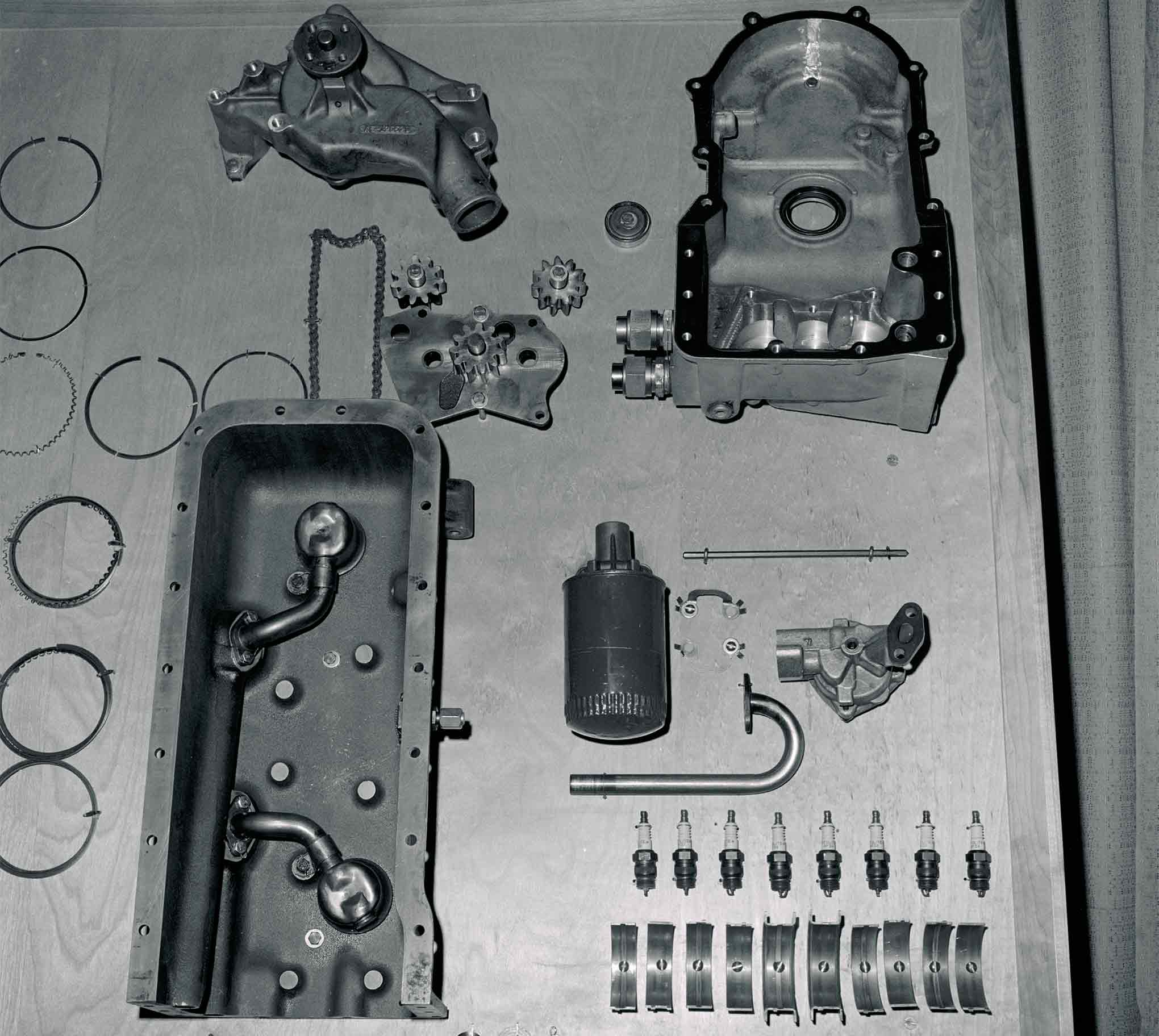 Virtually every component seen is either aluminum or, as in the case of the oil pan, magnesium. All are expensive and highly collectible today. The upper-right casting is the front cover, which ties into the oil pan at the front of the block. The aluminum water pump nests over the upper portion of the cover. Combustion chambers in the heads were fully machined.
